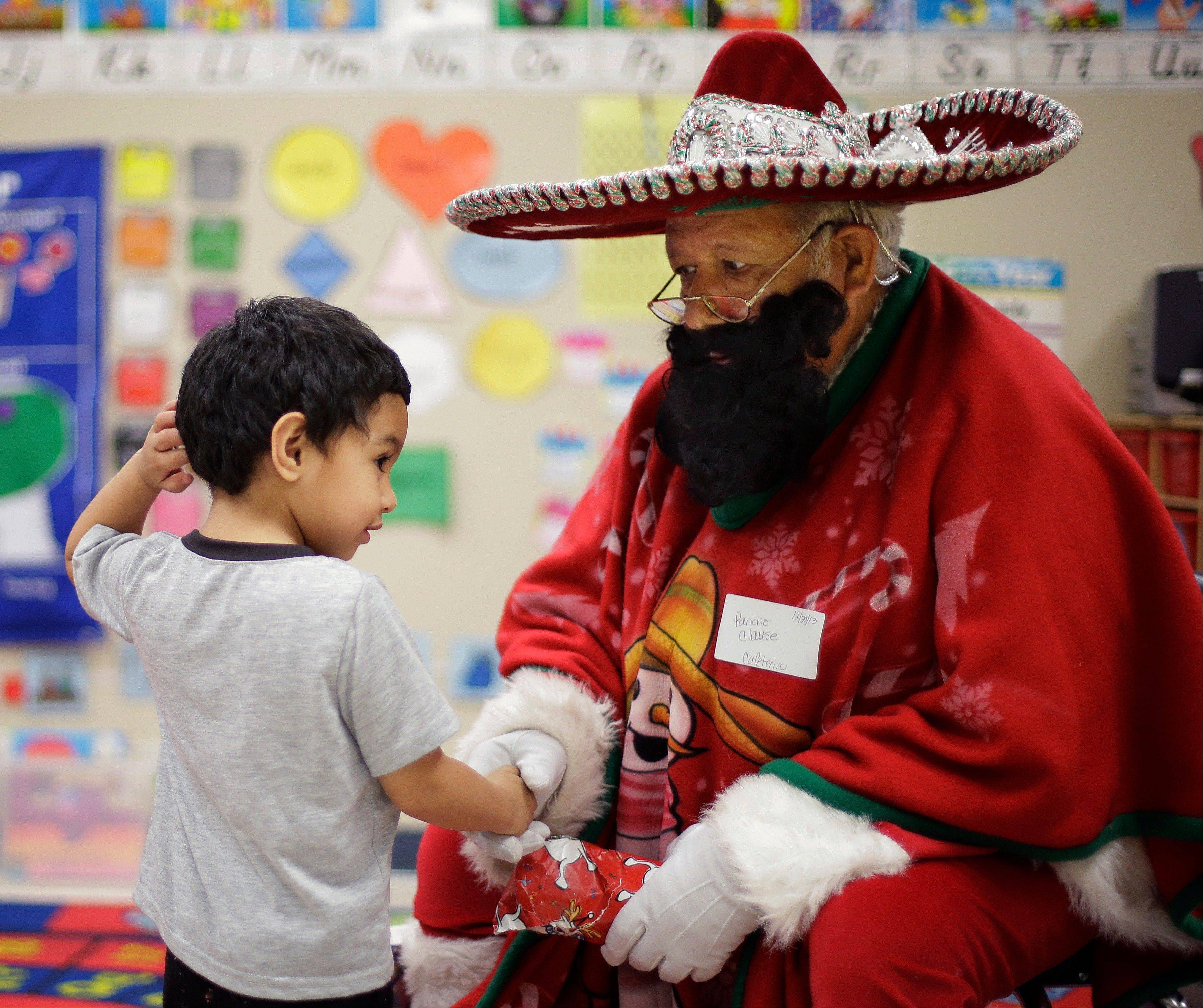 Pancho Claus, Rudy Martinez, right, visits with students at Knowlton Elementary School, in San Antonio. Pancho Claus, a Tex-Mex Santa borne from the Chicano civil rights movement in the late 1970s and early 1980s, is now an adored Christmas fixture in many Texas cities.