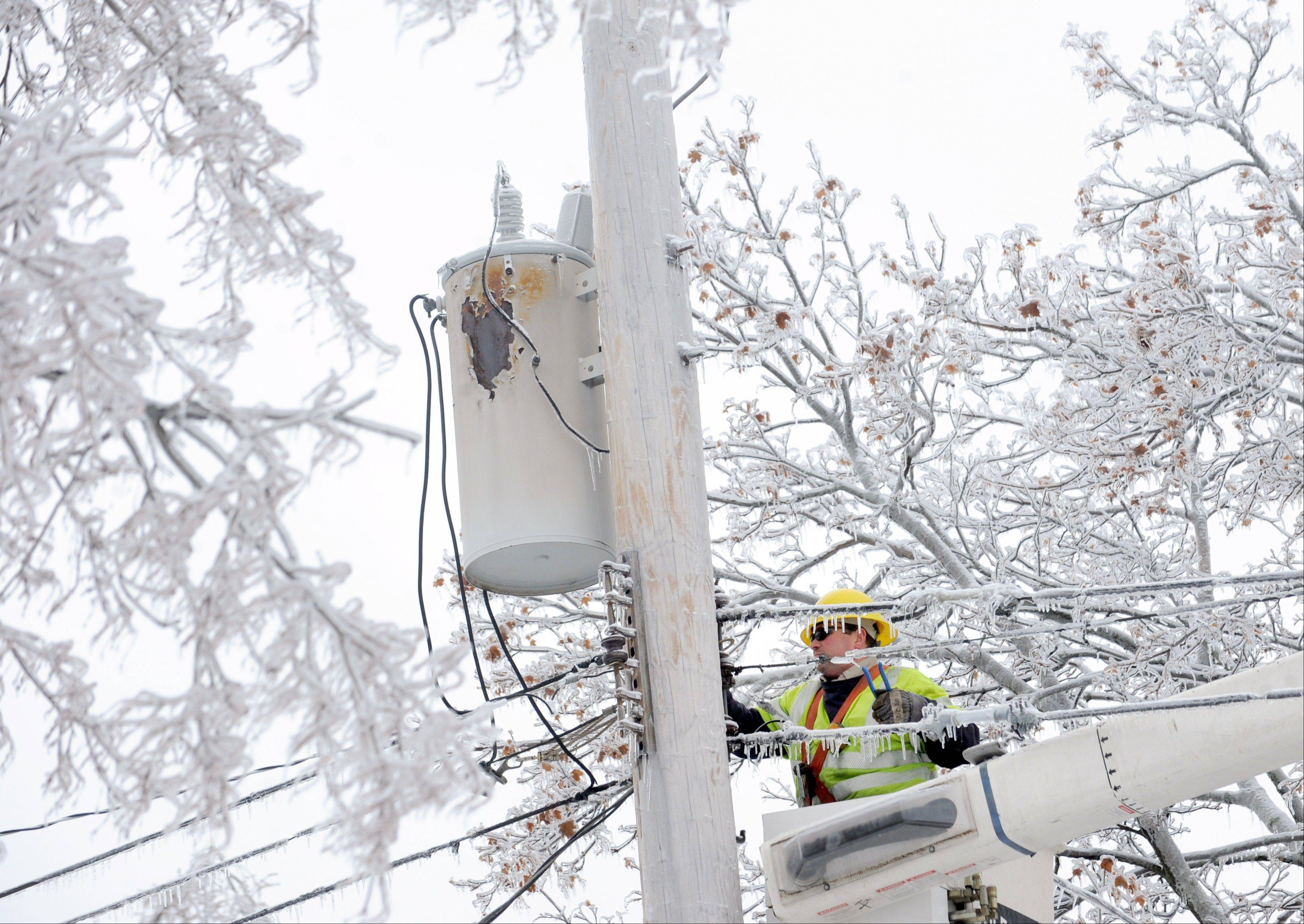 Dave Dora, a lineman from Grand Haven Board of Light and Power, works Monday on connecting fallen wires on Macon Avenue in Lansing, Mich.