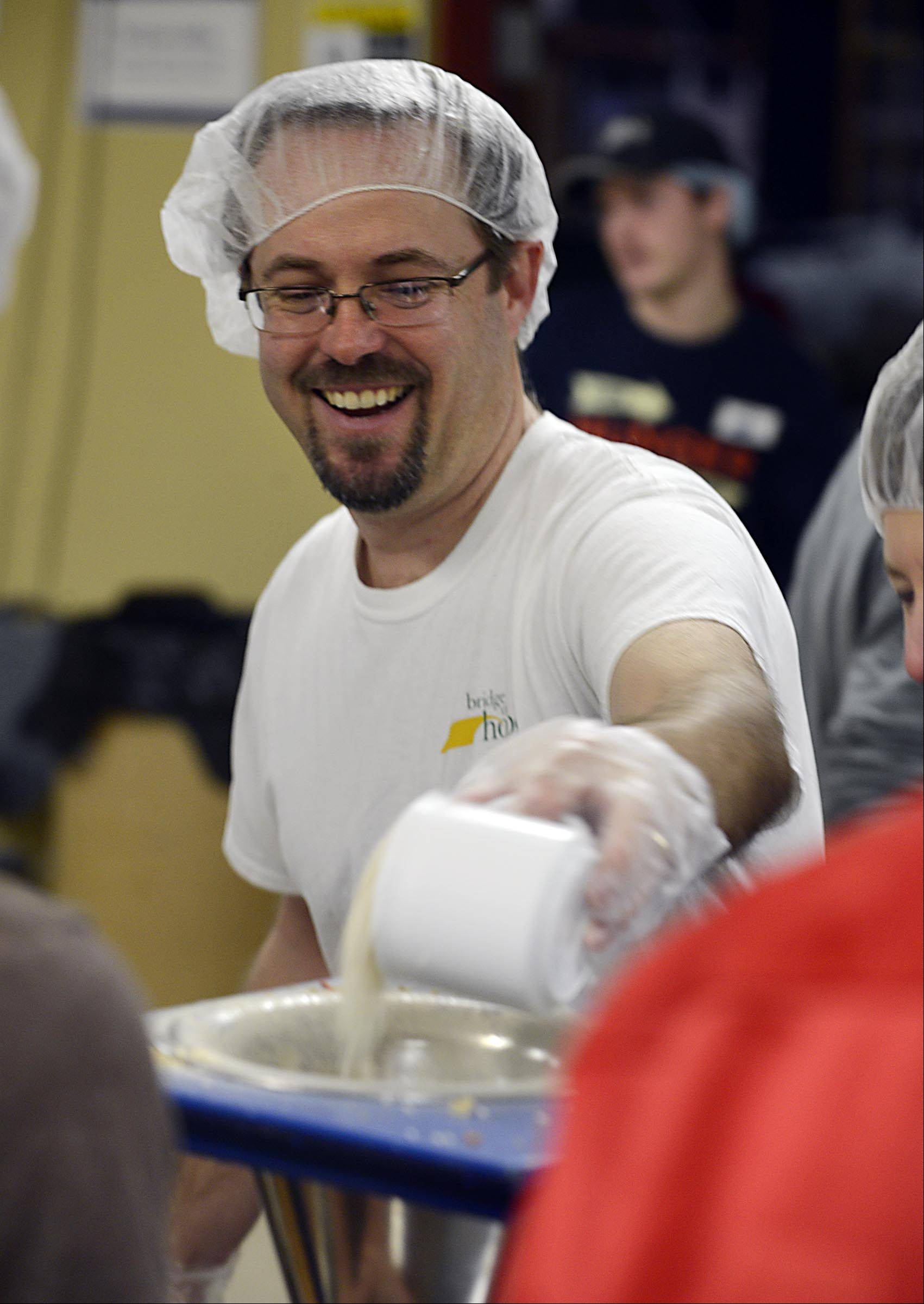Matt Burgess, of Champaign, enjoys the day with his Geneva family, as he measures rice and helps assemble food packets for hungry kids in Haiti and Cambodia.