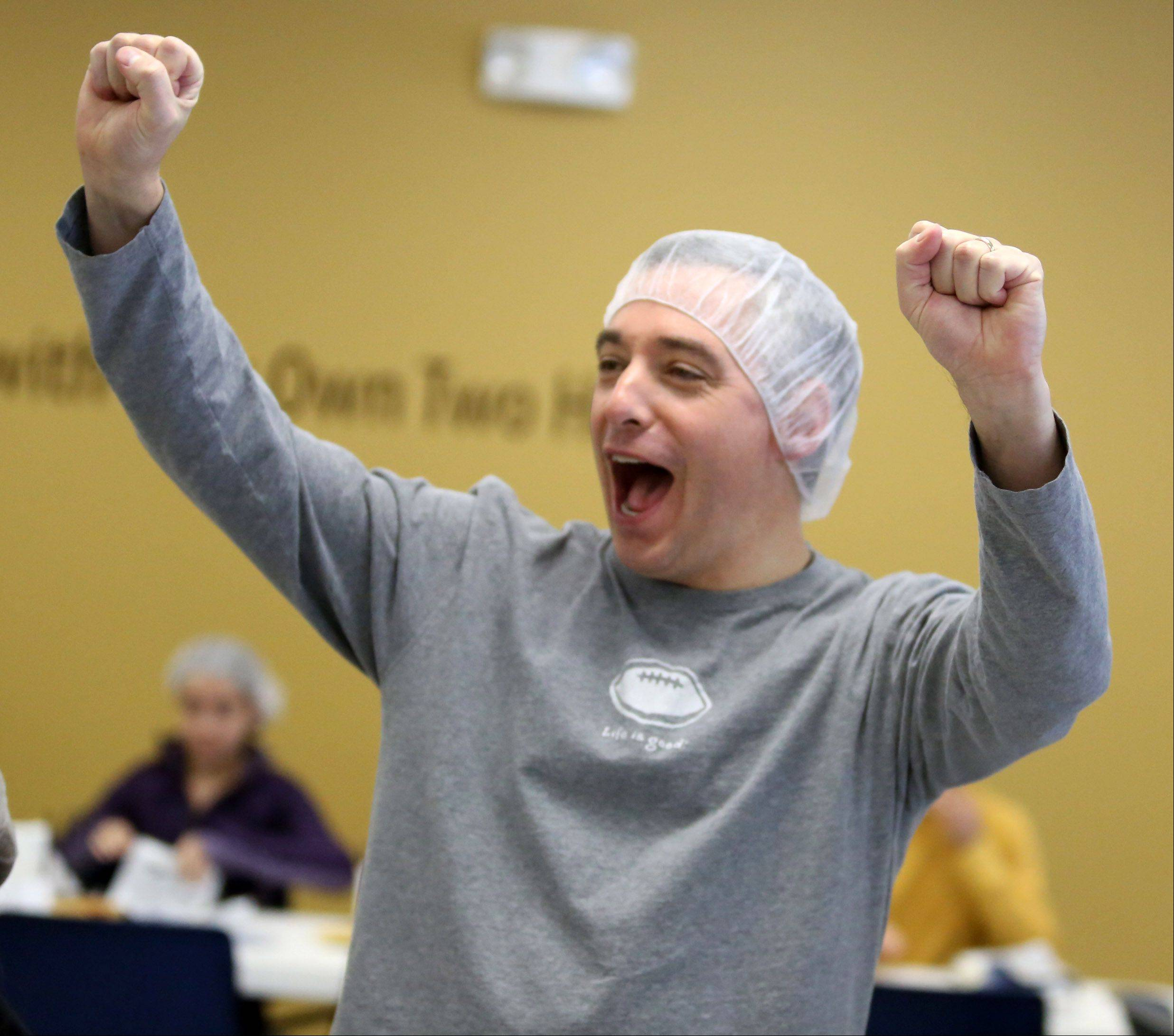 Javier Rodriguez, of Lake Forest, lets out a cheer for his family group as they pack food Tuesday in Libertyville.