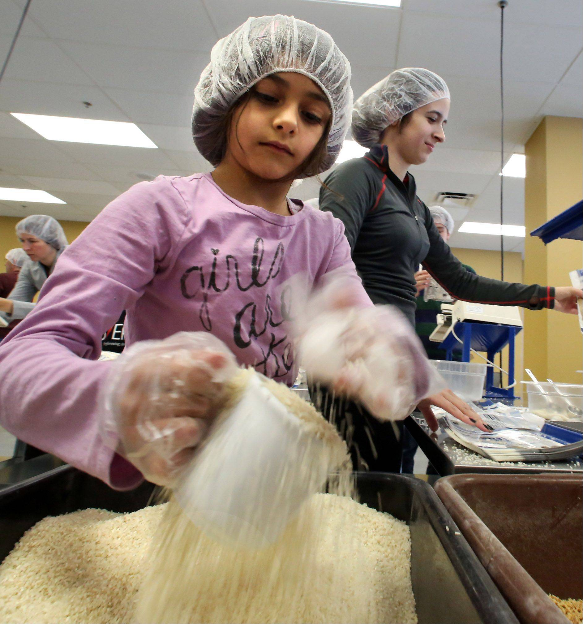 Seven-year-old Isabella Rodriguez scoops rice to pour into a meal packet, with Tesa Kubicek, both of Lake Forest, in background.