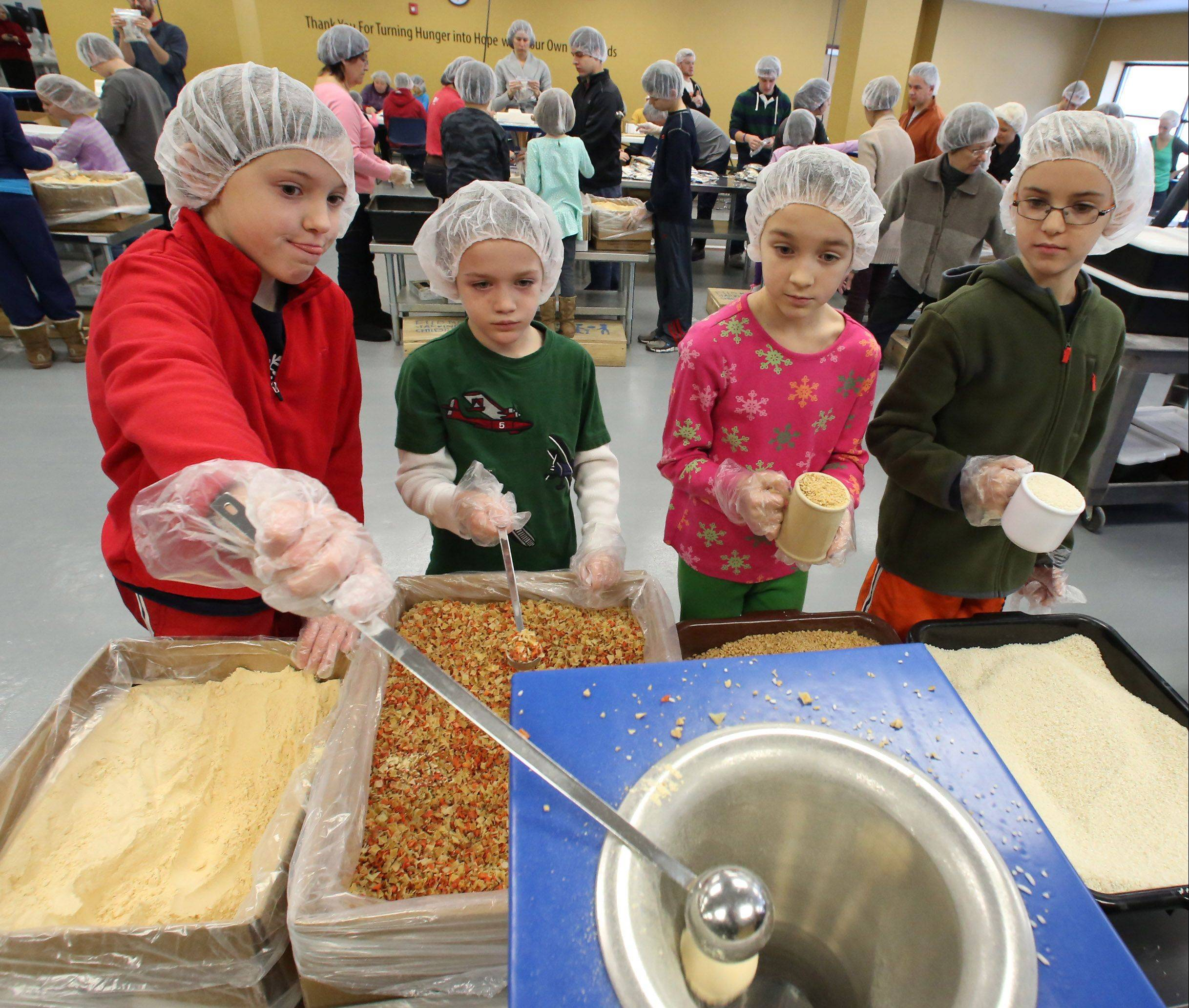 At left, Megan Roberts, 8, pours an ingredient into a meal-packet, as, from left, Davis Hillback, 6, Abbie Hillback, 8, and Jonah Roberts, 8, all of Libertyville, wait their turn. The food packets will be sent to hungry kids in Haiti and Cambodia.
