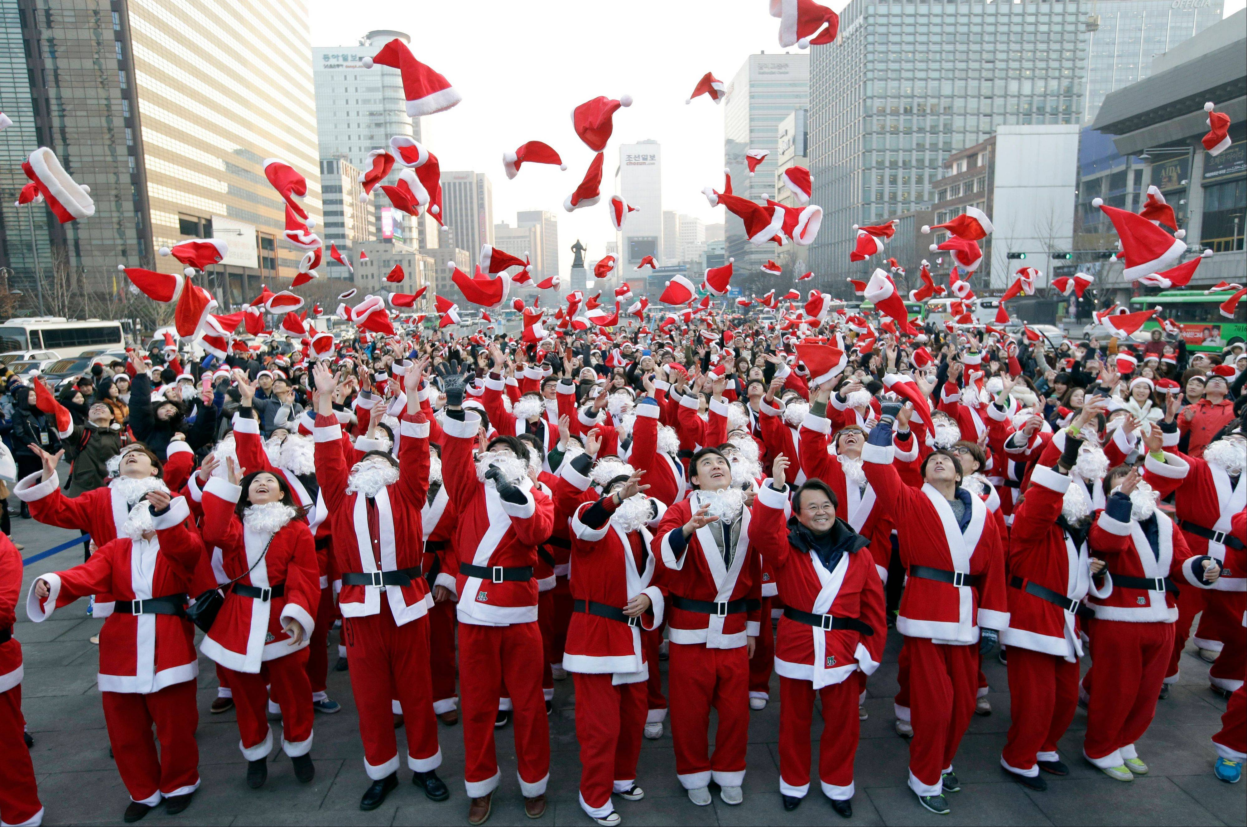 More than 1,000 volunteers clad in Santa Claus costumes throw their hats in the air as they gather to deliver gifts for the poor in downtown Seoul, South Korea, Tuesday, Dec. 24, 2013.