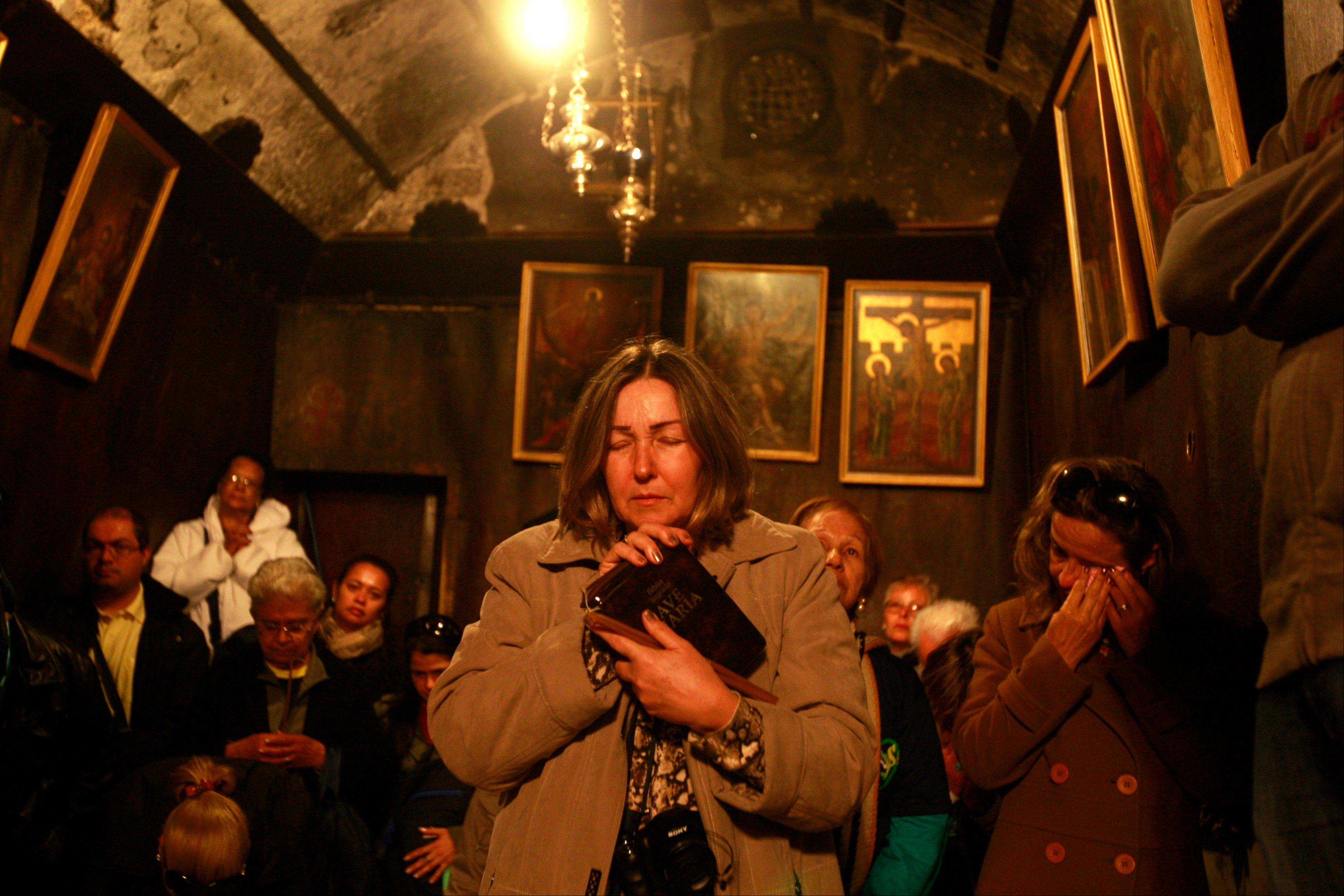 Christians pilgrim worshippers visit the Grotto of the Church of Nativity, traditionally believed by Christians to be the birthplace of Jesus Christ, in the West Bank town of Bethlehem on Christmas Eve, Tuesday, Dec. 24, 2013.