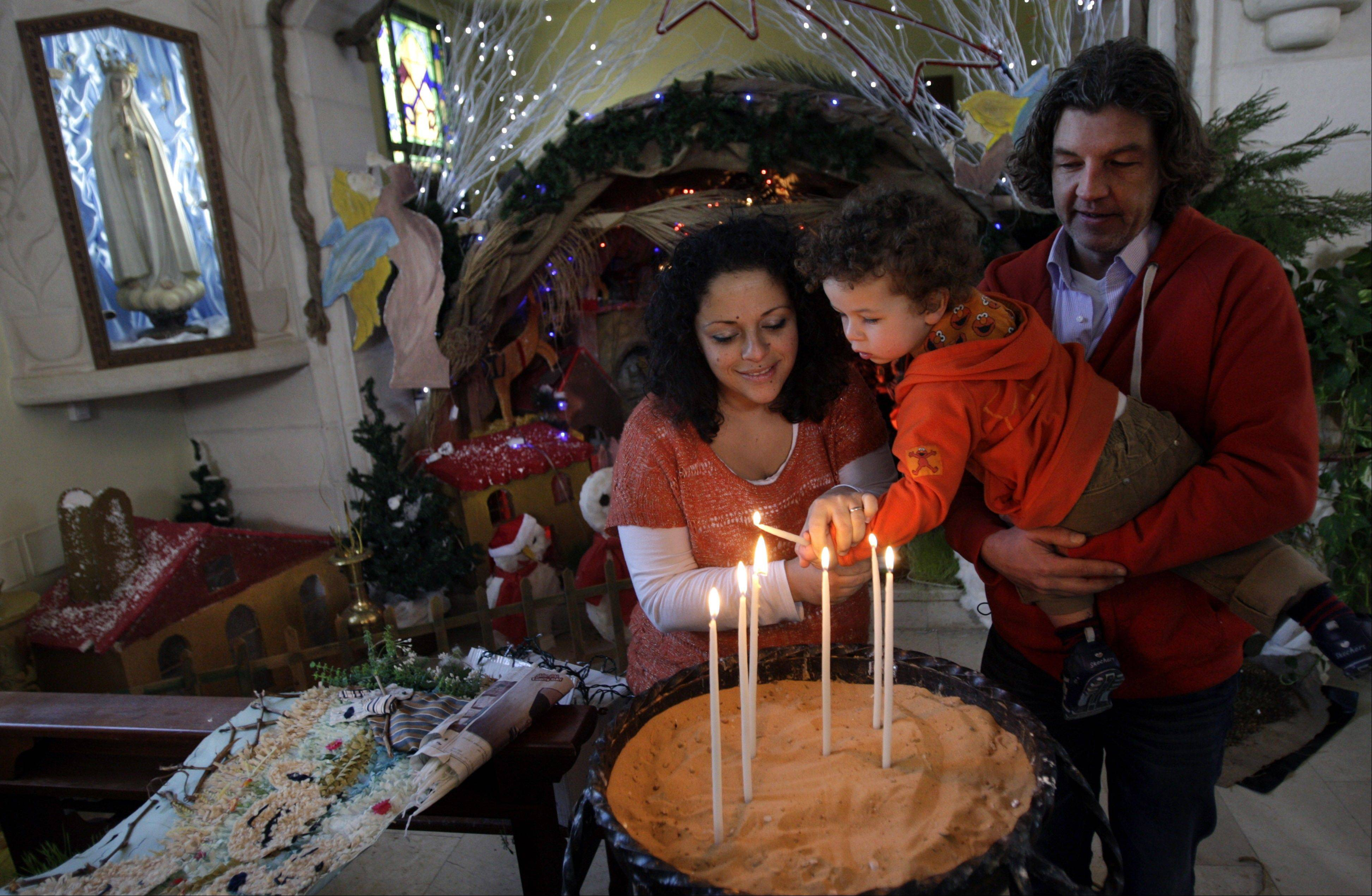 A Dutch family, light candles in front of a Nativity scene at the Latin Patriarch of Jerusalem Church of Visitation, also known as St. Mary's Visitation Church, in preparation for Christmas in the northern West Bank village of Zababdeh near Jenin, Tuesday, Dec. 24, 2013.