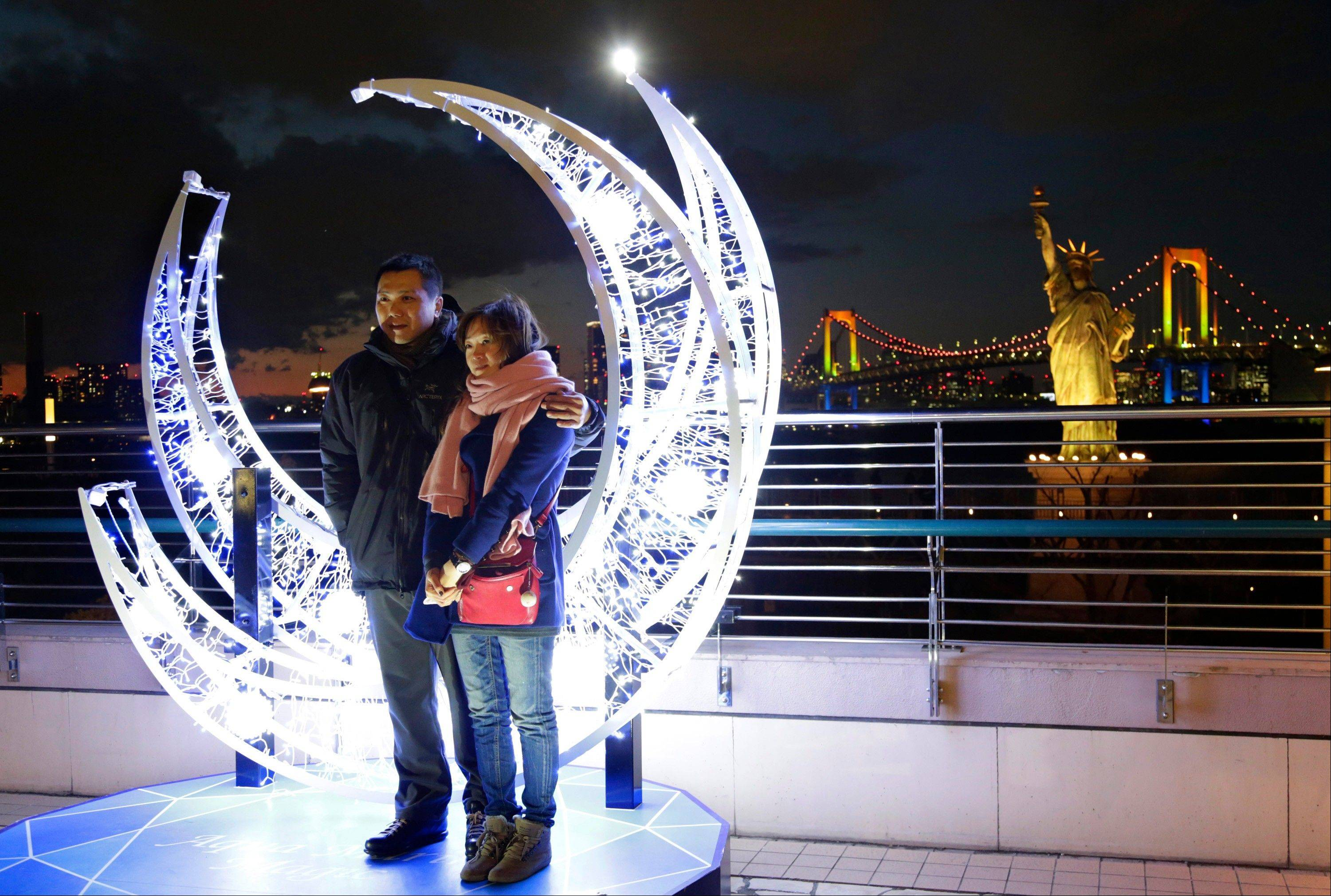 A couple poses in front of the Christmas illuminations for souvenir photos at Tokyo's Daiba bay area, Tuesday, Dec. 24, 2013.