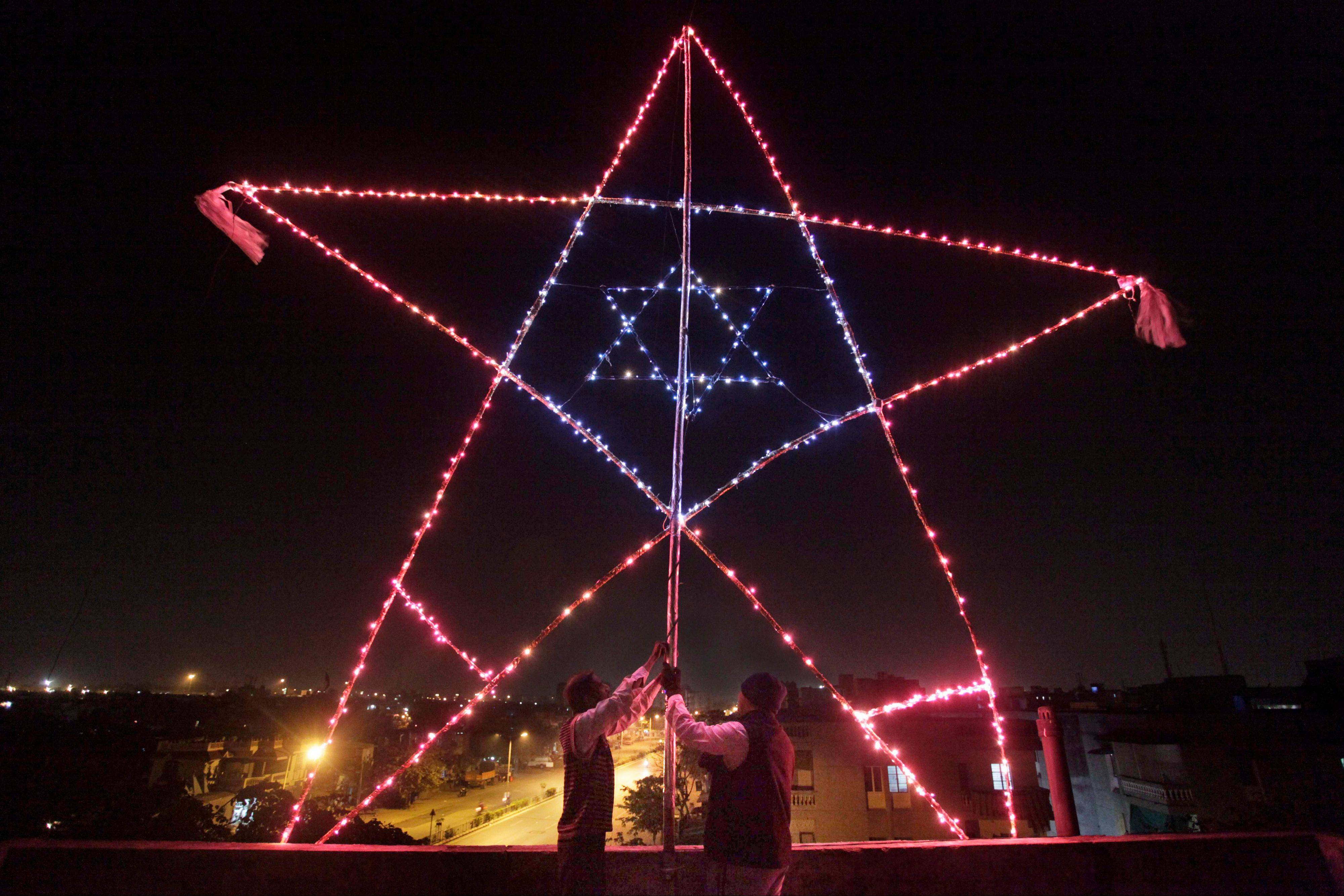In this Monday Dec. 23, 2013, photo, Indian Christians illuminate a 23 feet (7 meter) huge star on the terrace of their residential building in Ahmadabad, India. Although Christians comprise only two percent of the Indian population but Christmas is a national holiday and is observed across the country as an occasion to celebrate.