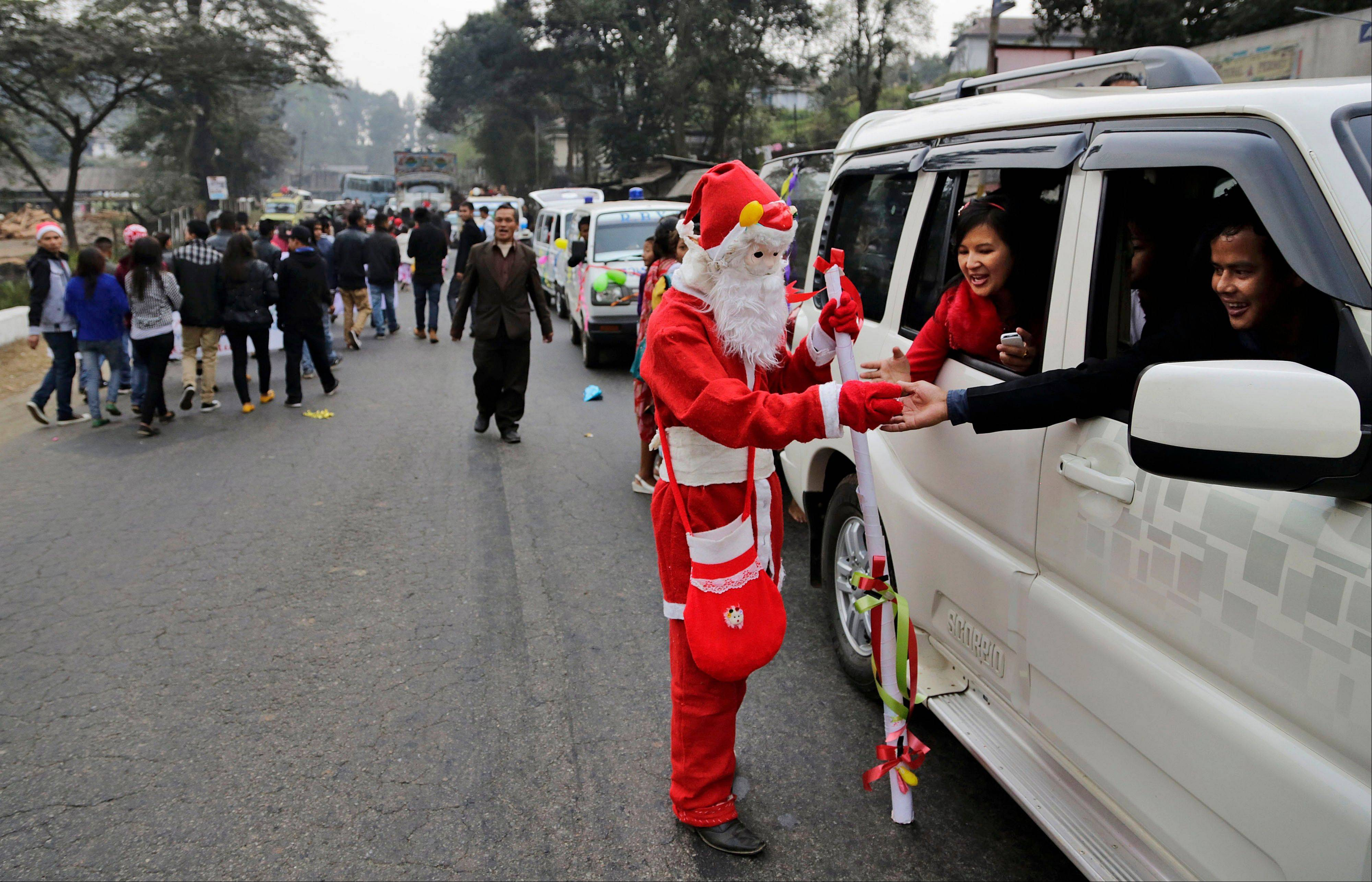 An Indian man dressed as Santa Claus distributes sweets among people in a car ahead of Christmas in Umsning, in Meghalaya, India, Tuesday, Dec. 24, 2013. Though Hindus and Muslims comprise the majority of the population in India, Christmas is celebrated with much fanfare.