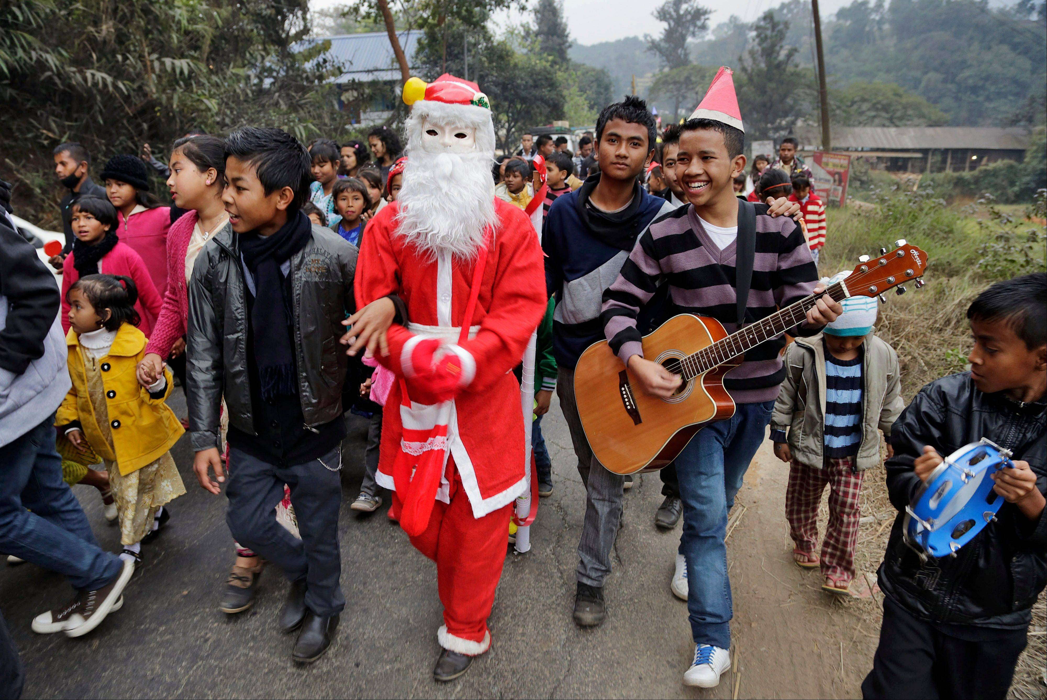 Indian people sing as they walk with a man dressed as Santa Claus ahead of Christmas in Umsning, in Meghalaya, India, Tuesday, Dec. 24, 2013. Though Hindus and Muslims comprise the majority of the population in India, Christmas is celebrated with much fanfare.