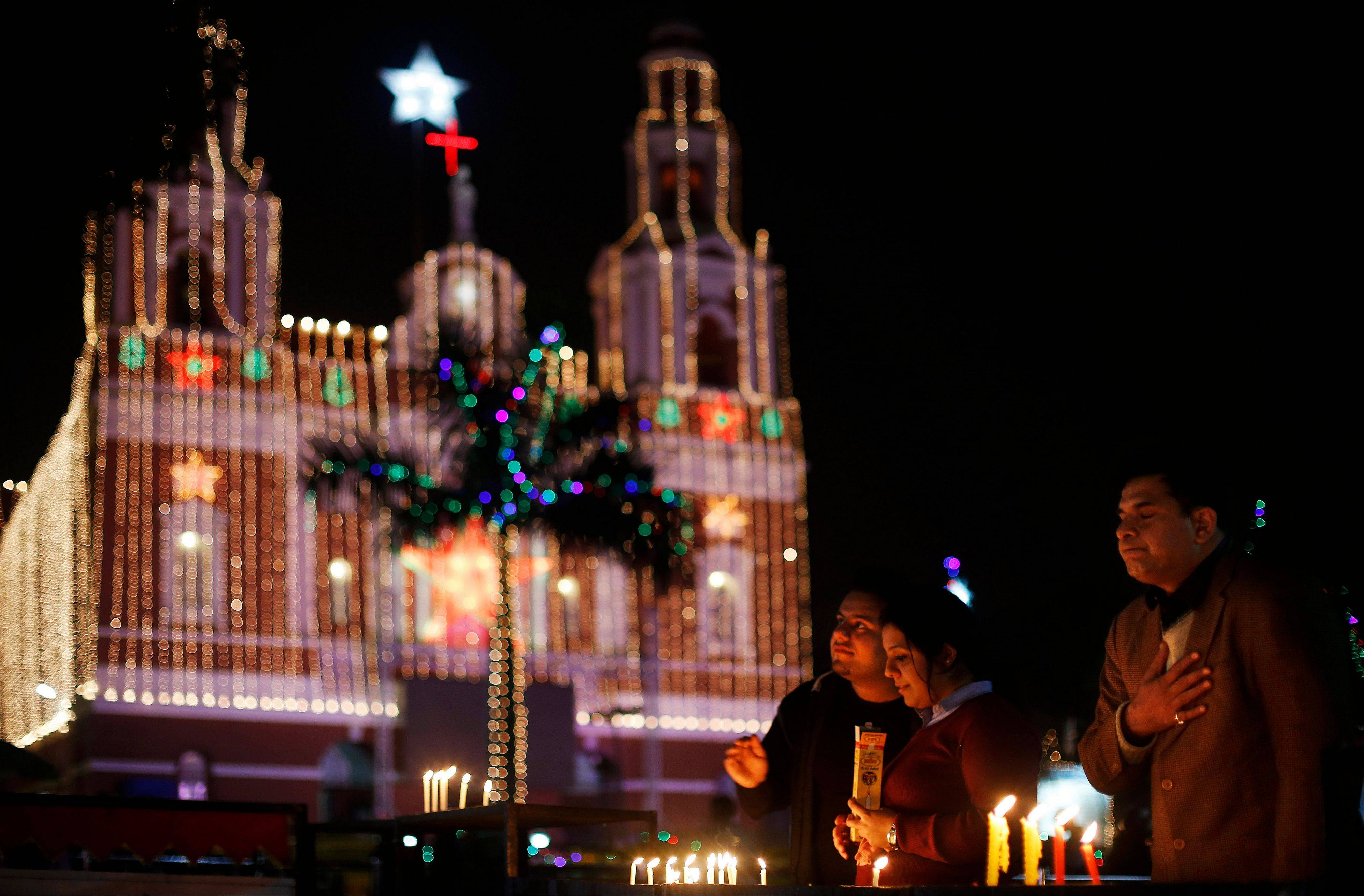 Indian Christian people light candles and pray at the illuminated Sacred Heart�s Cathedral on Christmas Eve in New Delhi, India, Tuesday, Dec. 24, 2013. Though Hindus and Muslims comprise the majority of the population in India, Christmas is celebrated with much fanfare.