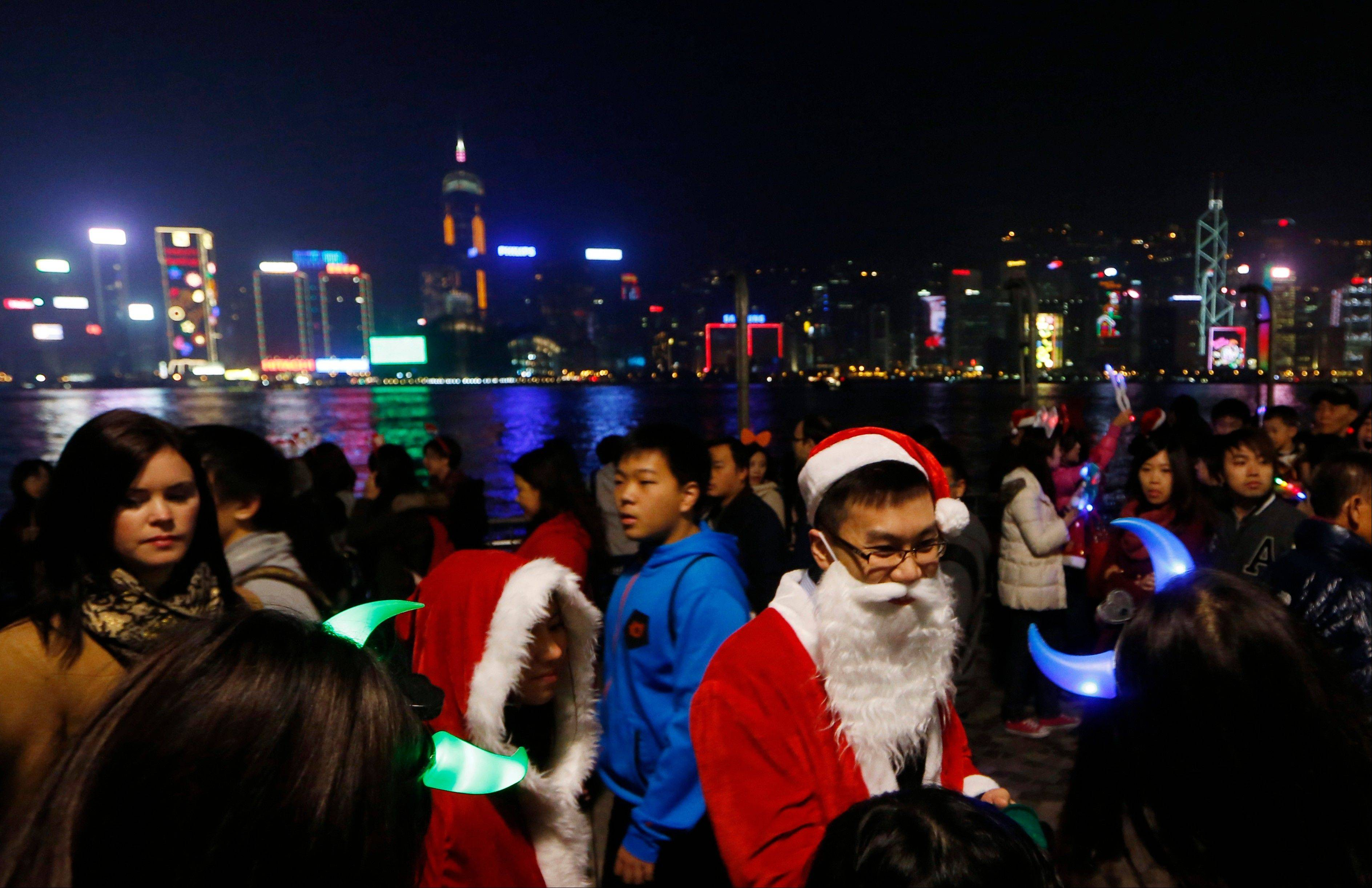 A couple dressed as Santa Claus deliver candies to visitors at the waterfront of Victoria Harbor in Hong Kong during Christmas eve as they are celebrating the festival season,Tuesday, Dec. 24, 2013.