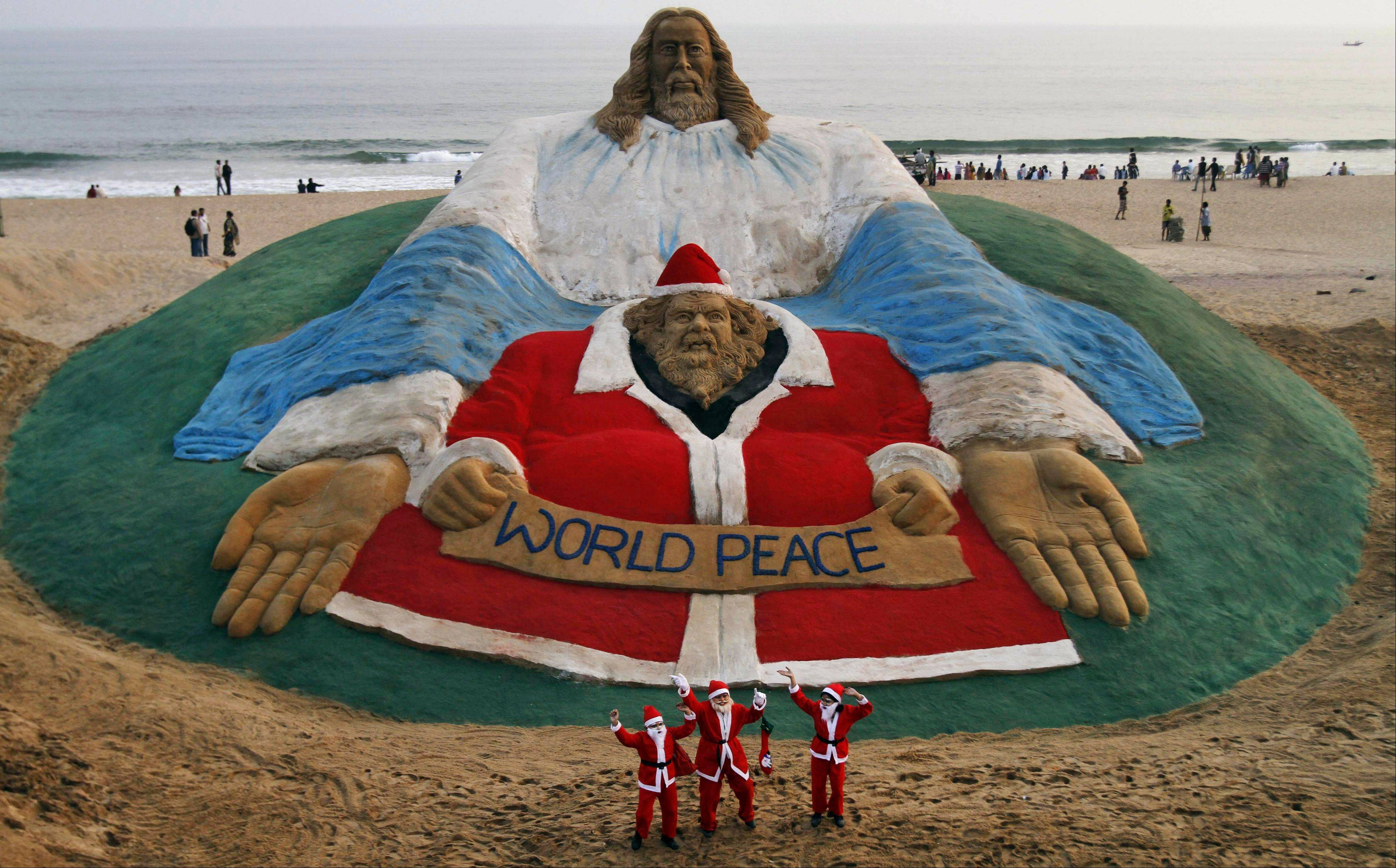 Indian children dressed as Santa Claus dance in front of a sculpture titled World Peace by sand artist Sudarshan Patnaik ahead of Christmas at a beach in Puri, in the eastern Indian city of Bhubaneswar, India, Tuesday, Dec. 24, 2013. Though Hindus and Muslims comprise the majority of the population in India, Christmas is celebrated with much fanfare.