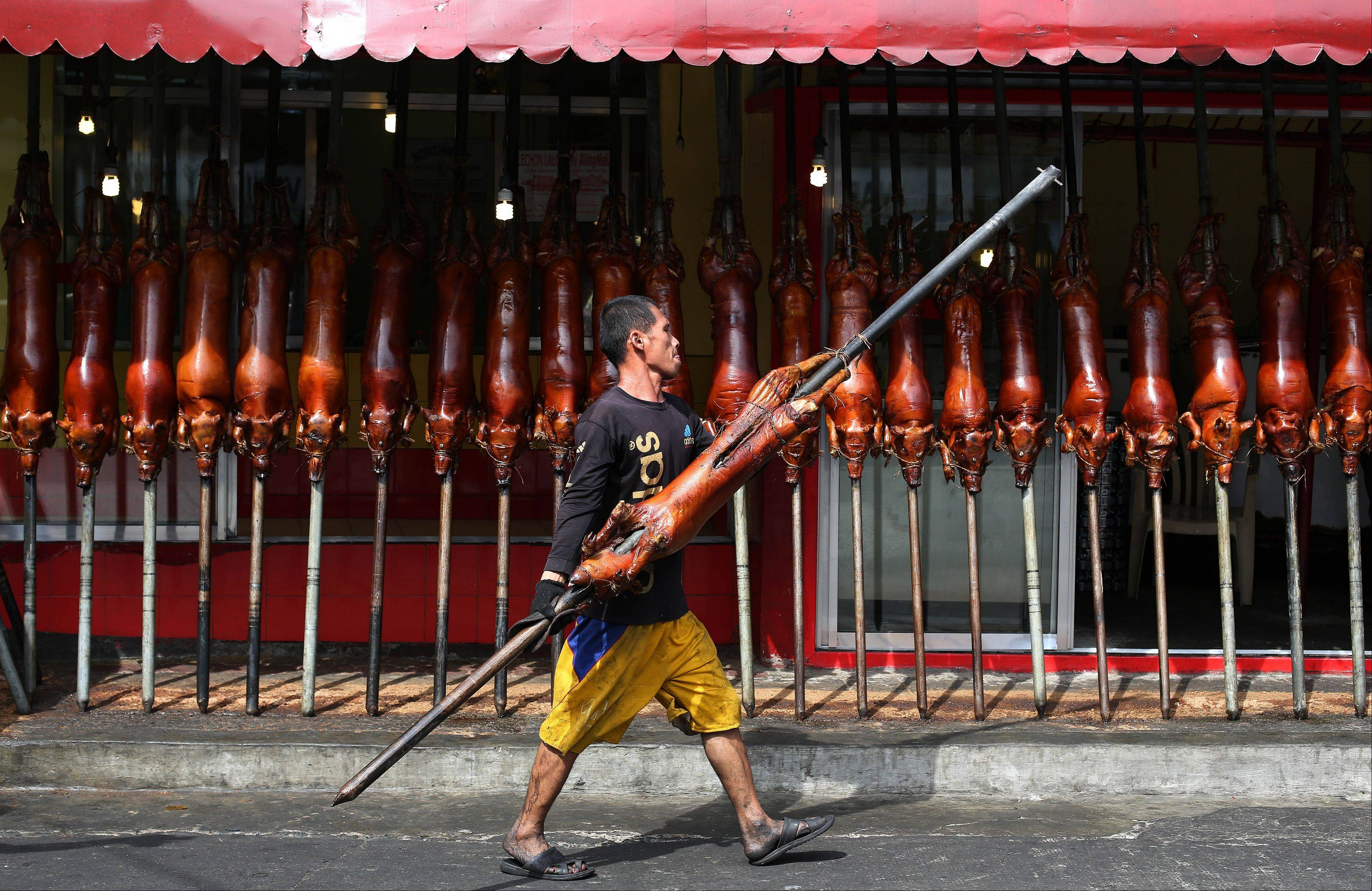 "A worker carries roasted pig outside a store in Quezon city, north of Manila, Philippines on Tuesday, Dec. 24, 2013. Roasted pig is traditionally served during a Christmas eve dinner called ""Noche Buena"" in this predominantly Roman Catholic nation."