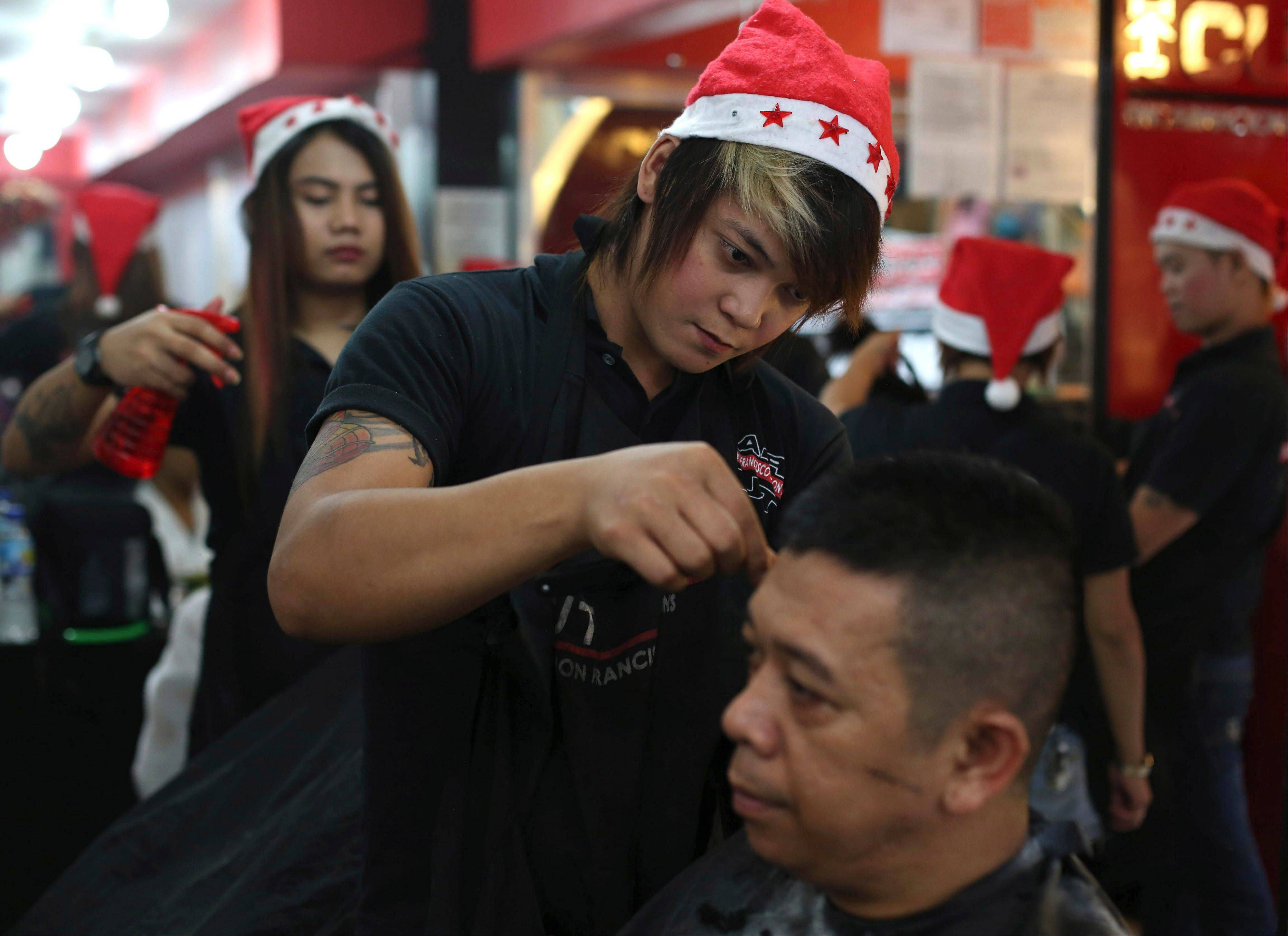 Filipino hairdressers wear Santa hats as they cut hair during Christmas eve at a shop in downtown Manila, Philippines on Tuesday, Dec. 24, 2013. Christmas is one of the most important holidays in this predominantly Roman Catholic nation.