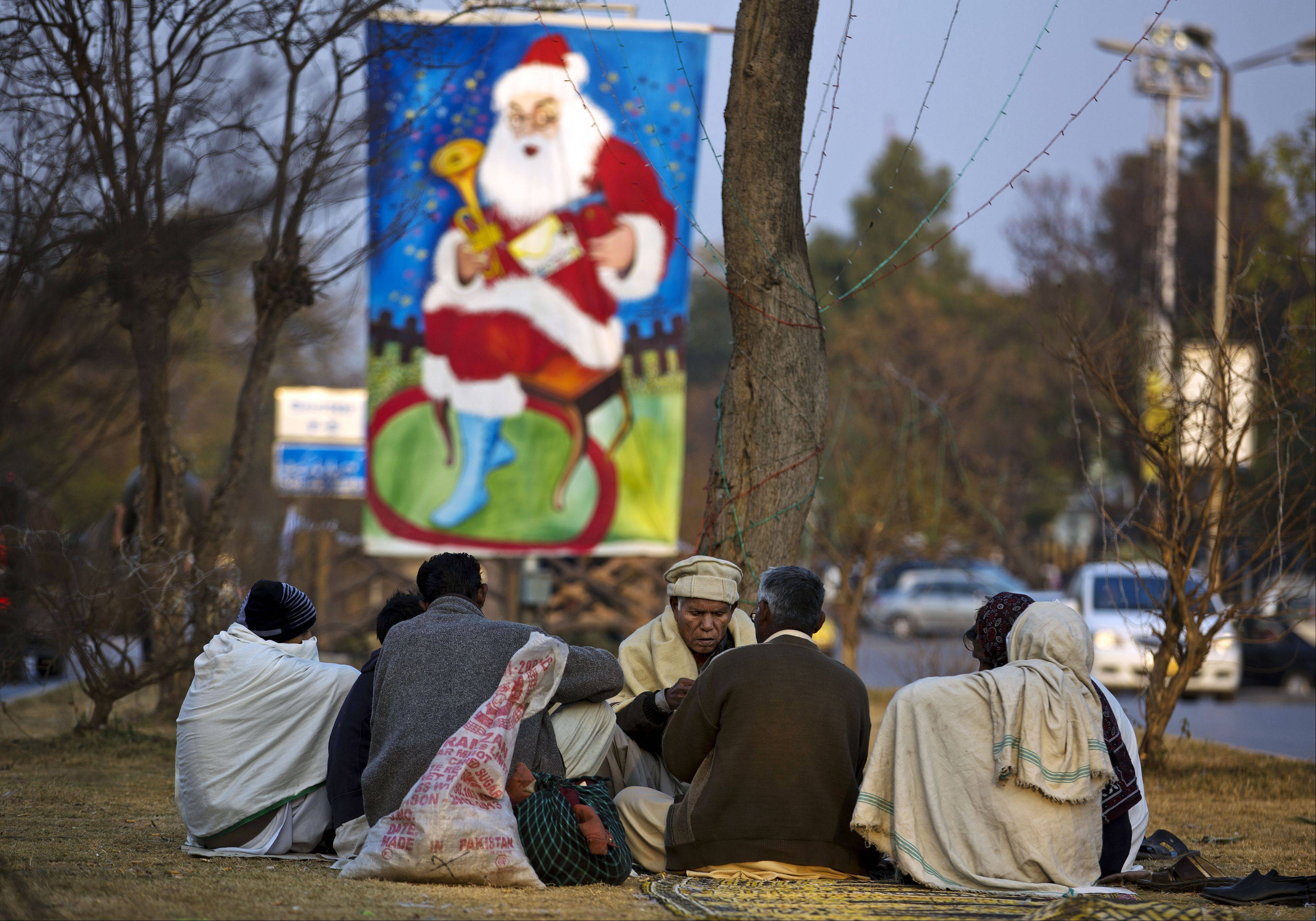 Pakistani Christians play cards on a roadside near their neighborhood ahead of Christmas in Islamabad, Pakistan, Tuesday, Dec. 24, 2013. Christians are a minority in Pakistan, they constitute about 1.6% of the Pakistan�s population.