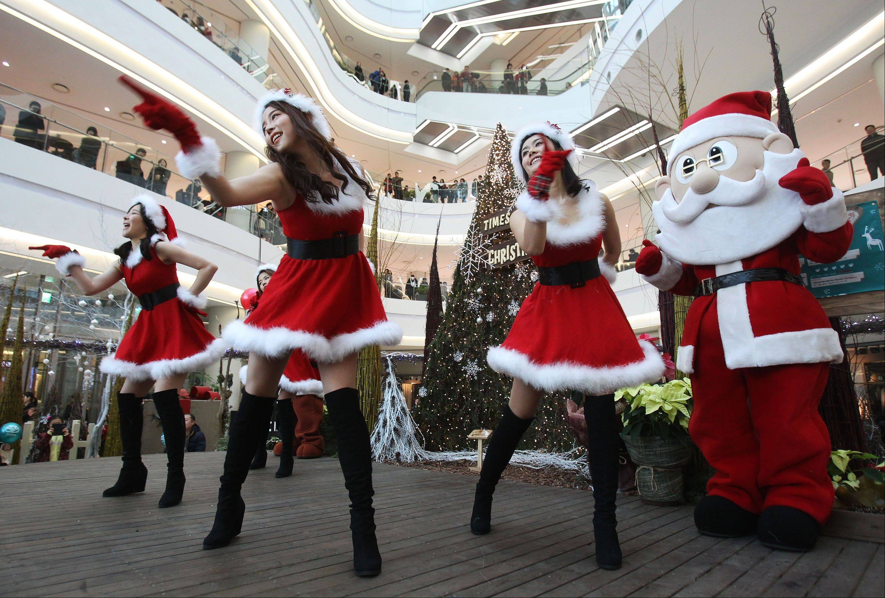 Employees dressed as Santa Claus perform as part of a shopping mall's Christmas celebrations in Seoul, South Korea, Tuesday, Dec. 24, 2013. A lot of South Korean companies take advantage of the Christmas to promote their business amid weak sales and economic slowdown.