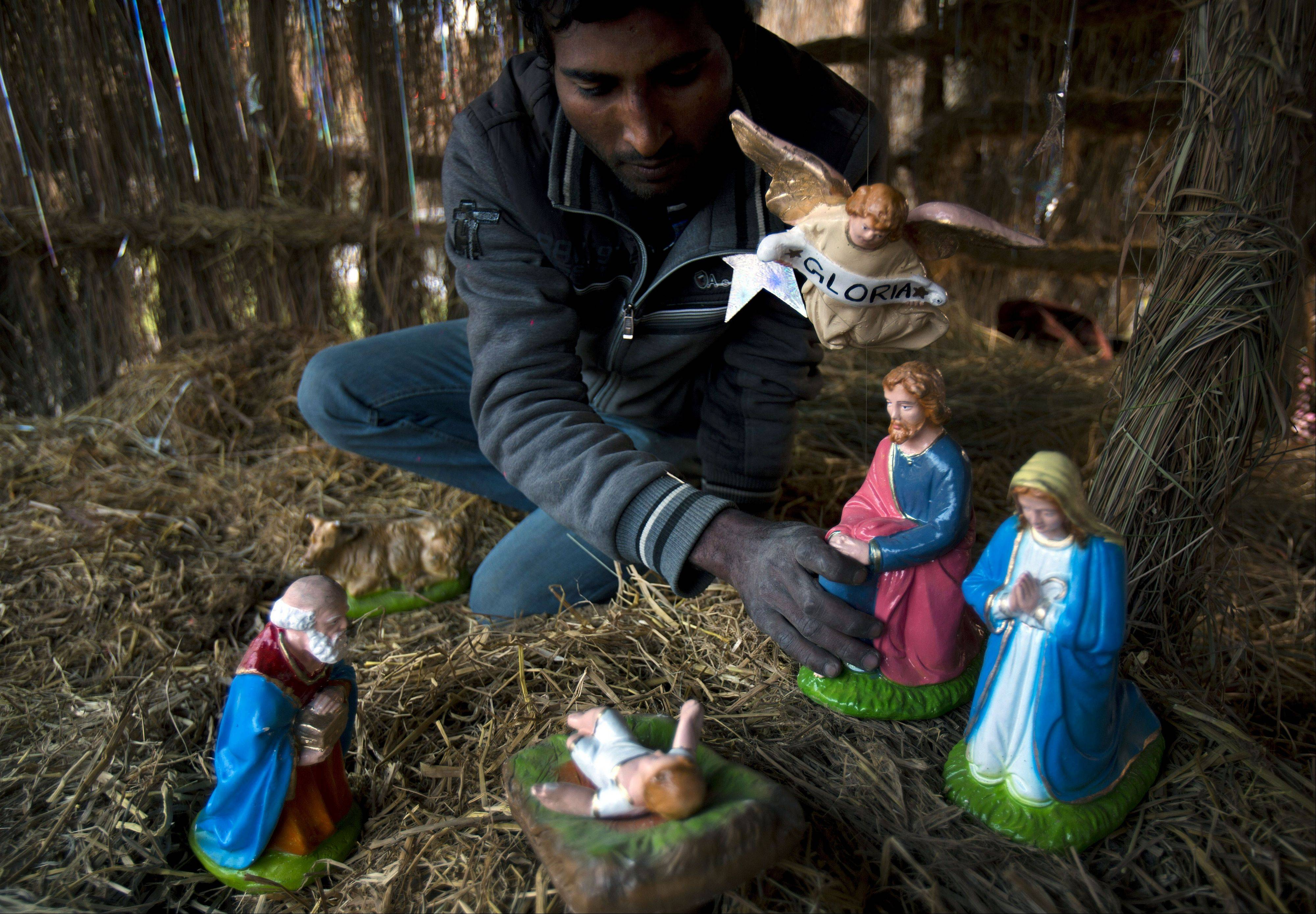 Pakistani Christian Salamat Masih prepares a scene of nativity for Christmas celebrations in the slums of Islamabad, Pakistan, Tuesday, Dec. 24, 2013. Christians are a minority in Pakistan, they constitute about 1.6% of the Pakistan�s population.