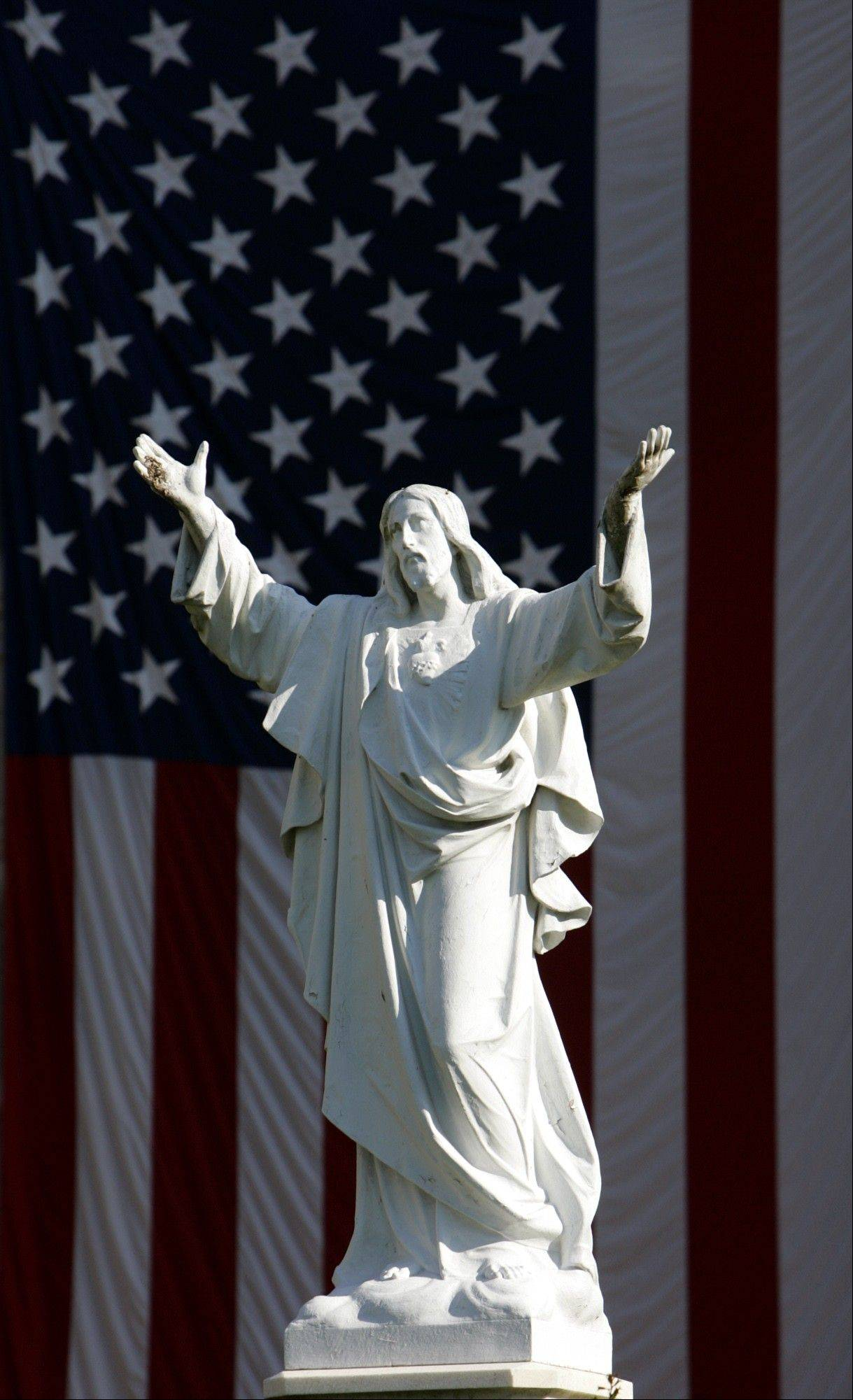 "A large American flag hangs at the Loyola University campus in New Orleans behind a life-size statue of Jesus Christ. In America, white Jesus images started to become widespread in the early 1800s, according to Edward Blum, co-author of ""The Color of Christ: The Son of God and the Saga of Race in America,"" coinciding with a dramatic rise in the number of slaves, a push to move Native Americans further west, and a growing manufacturing capability. Today, a white Jesus image is ingrained in American culture."