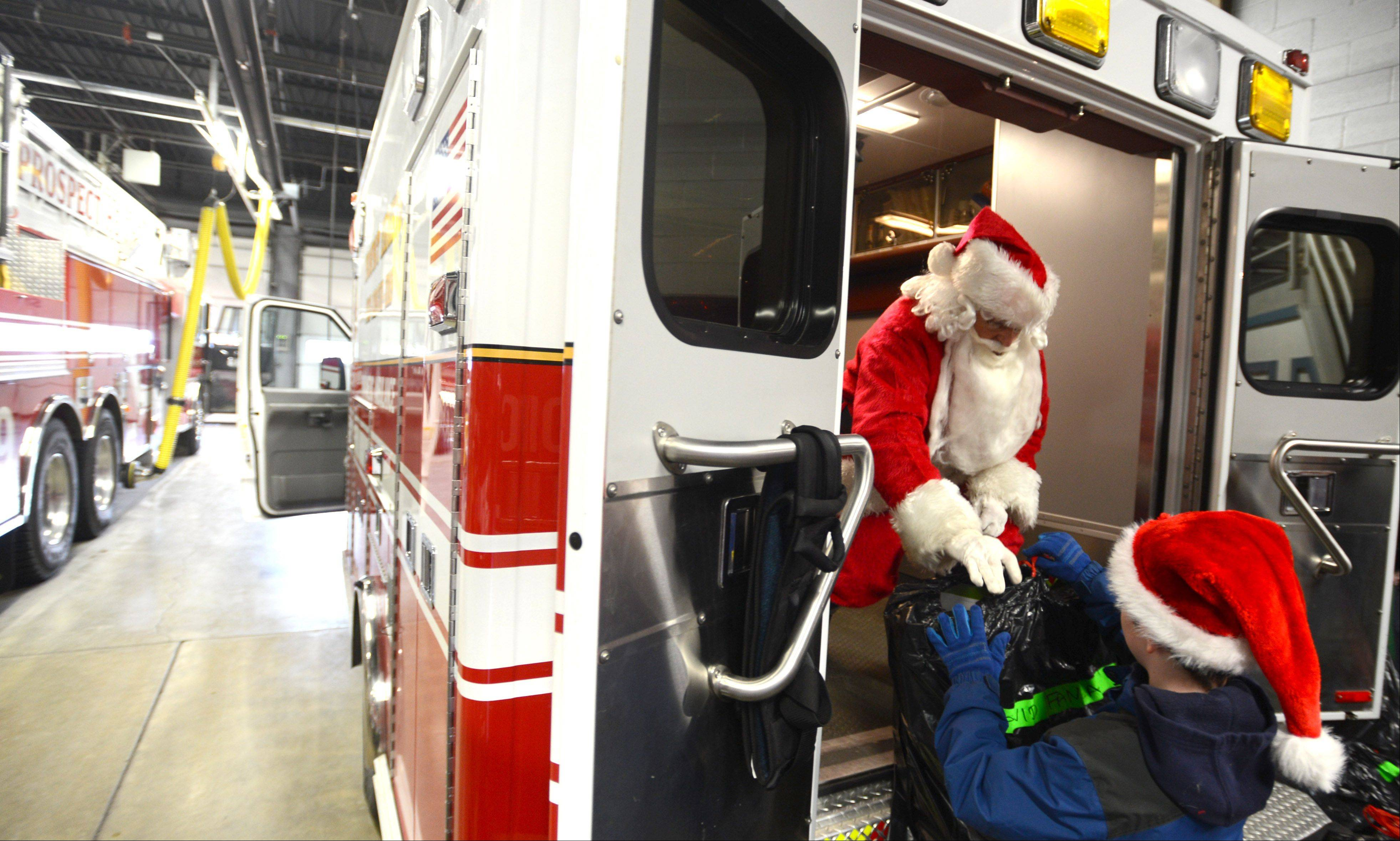 Santa Claus receives assistance Monday from volunteer Brandon Suerth, 9, of Prospect Heights as they load Christmas gifts into an ambulance for delivery to local families in need.