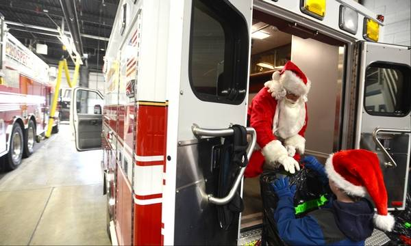 Santa joins prospect hts police fire on special deliveries santa claus receives assistance monday from volunteer brandon suerth 9 of prospect heights as spiritdancerdesigns Gallery
