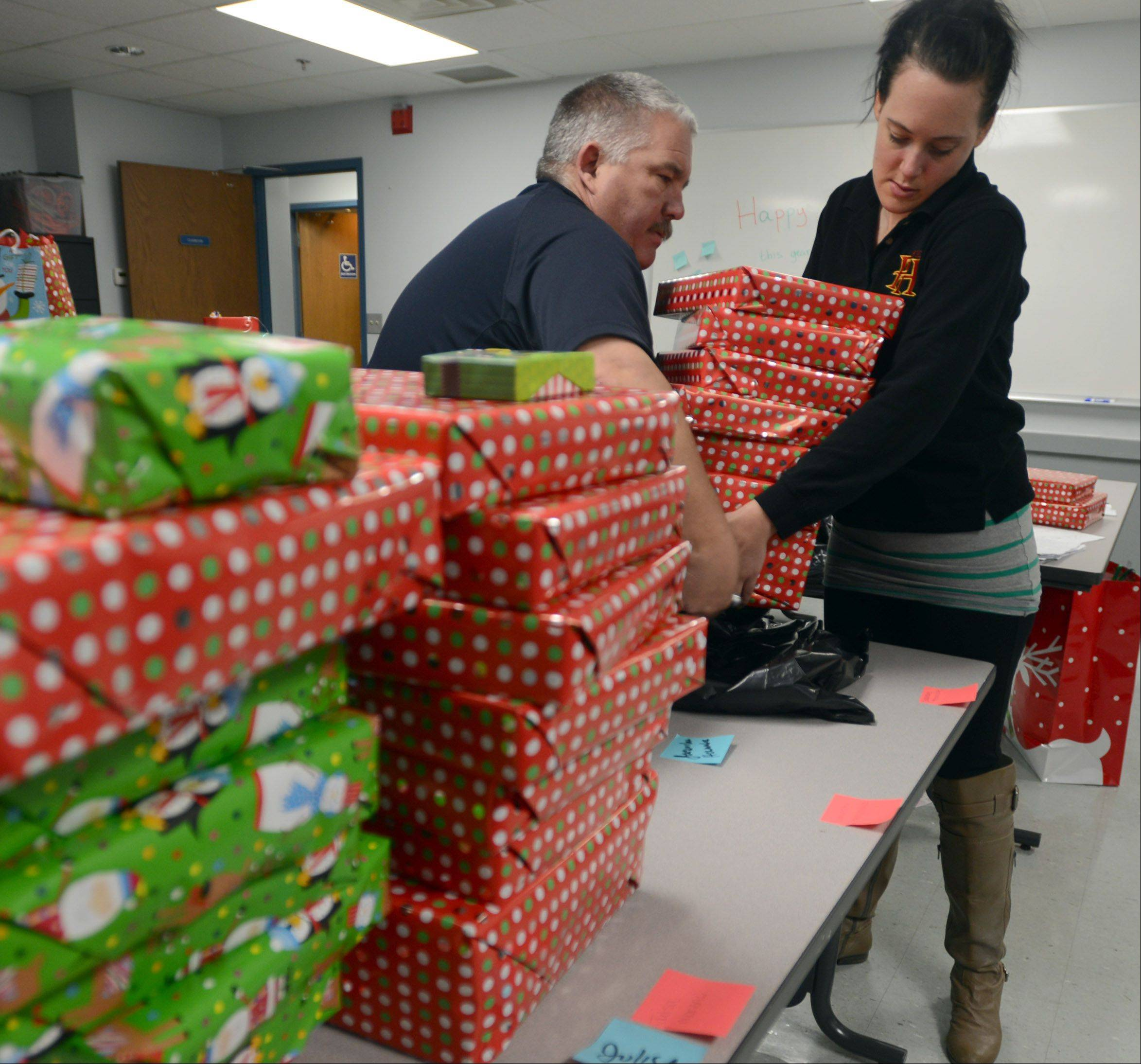 Prospect Heights Deputy Fire Chief Timothy Jones, left, and administrative assistant Lauren Clausen load Christmas gifts for delivery on Monday afternoon.