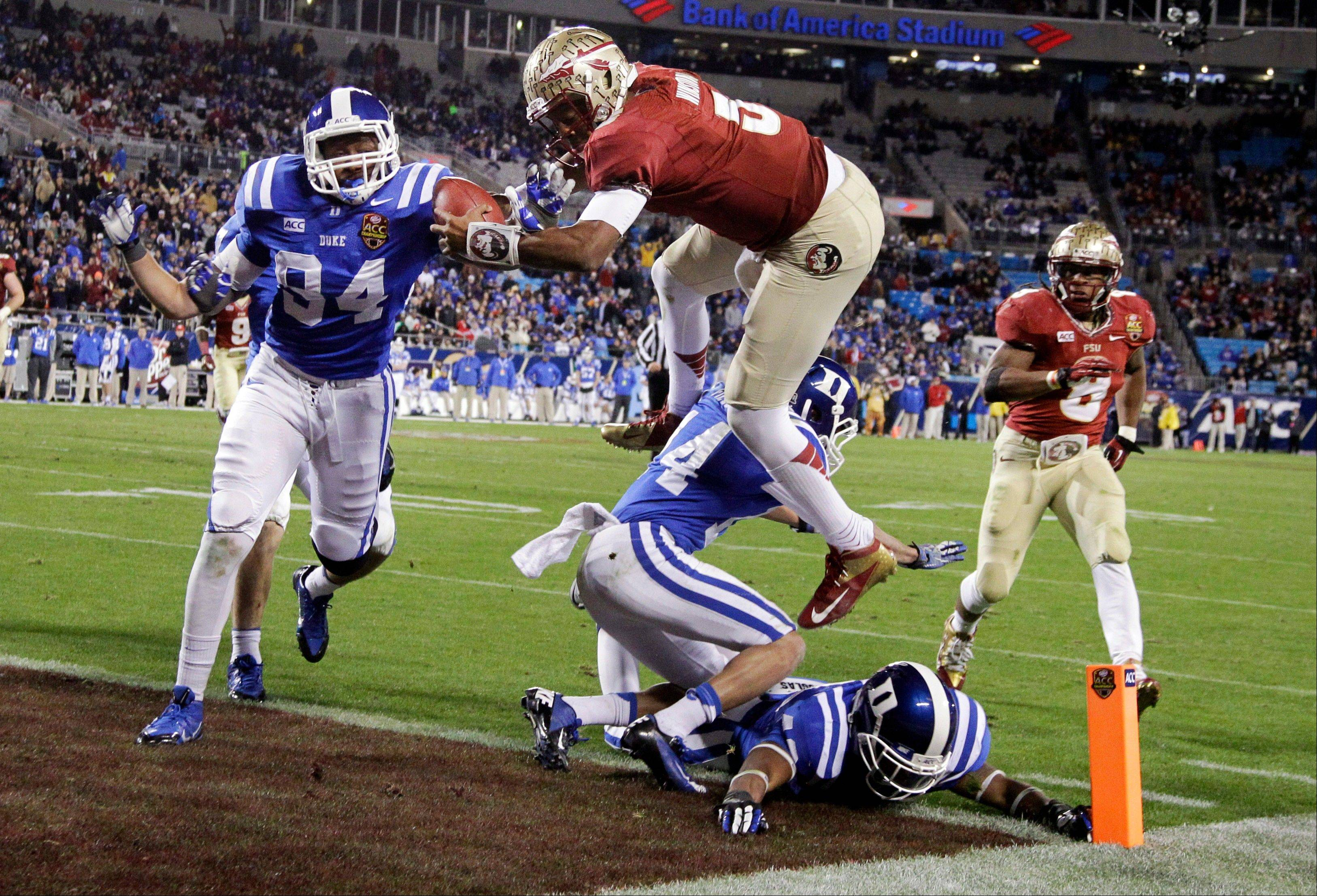 In this Dec. 7 file photo, Florida State's Jameis Winston (5) leaps over Duke's Bryon Fields (14) for a touchdown in the second half of the Atlantic Coast Conference Championship NCAA football game in Charlotte, N.C. The Associated Press on Tuesday named Winston its player of the year.