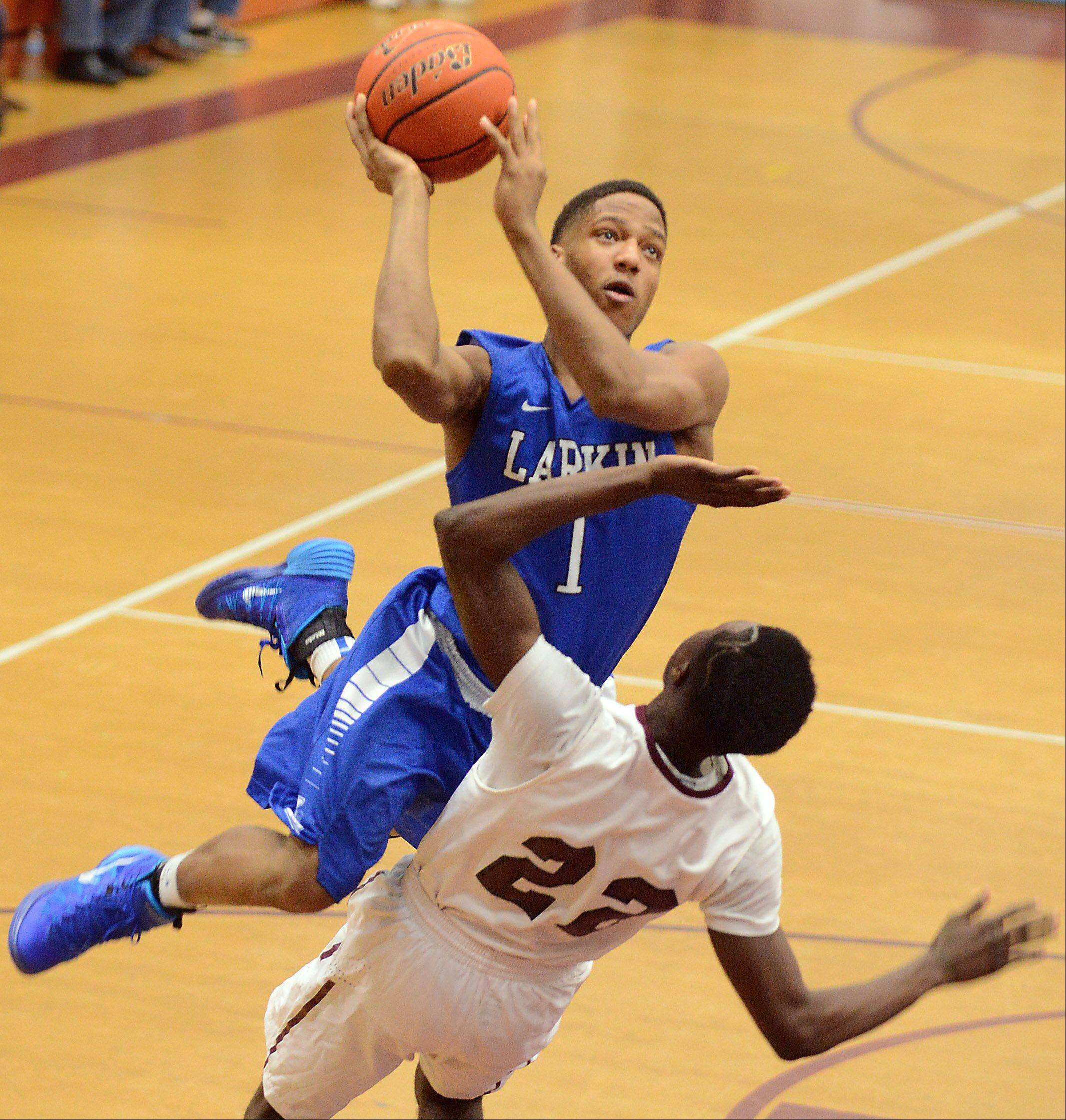 Larkin's Charles Sanders (1) drives over Elgin's Desmond Sanders (22) during Thursday's game in Elgin.