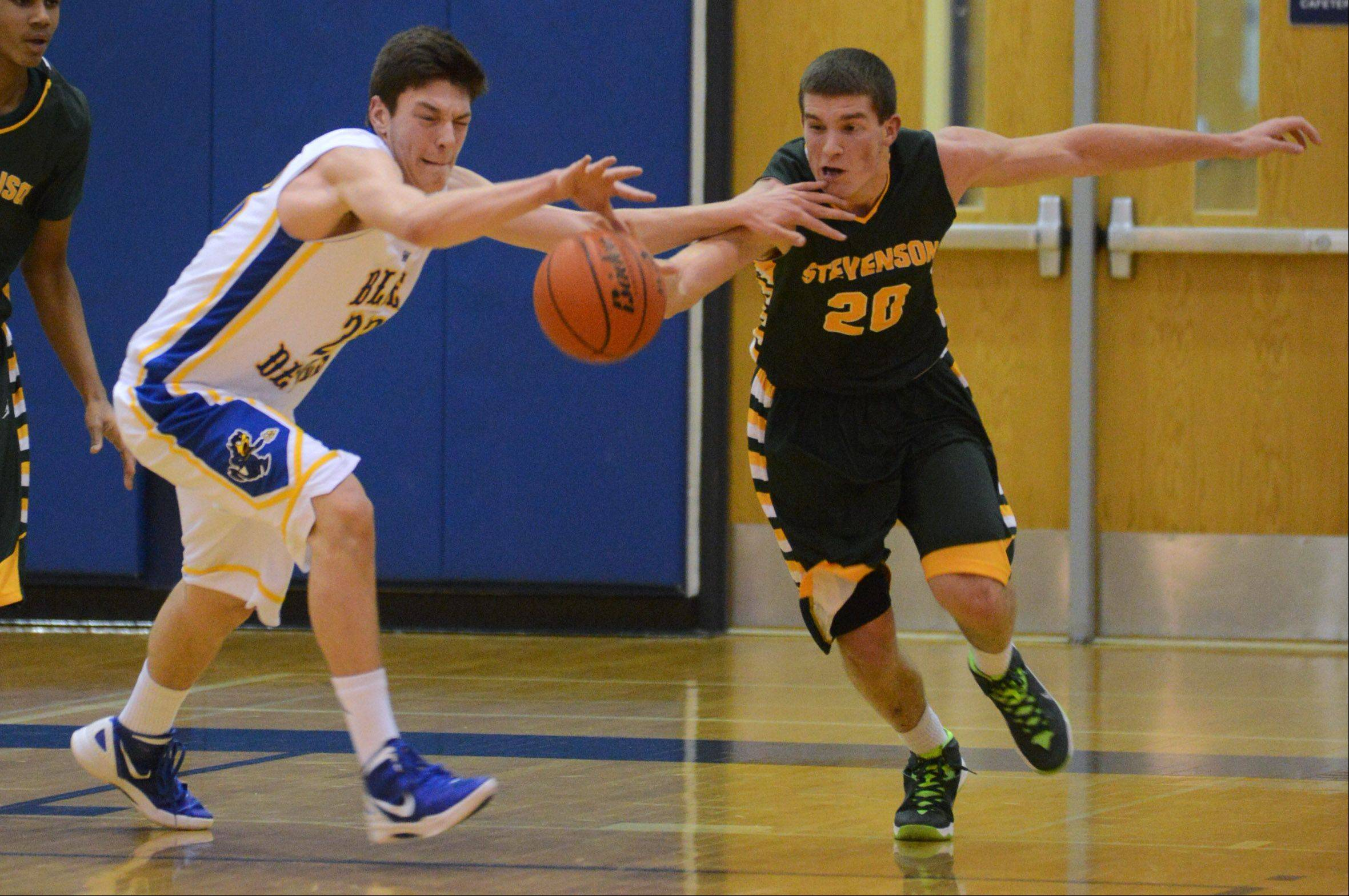 Warren's Jovan Jokic, left, and Stevenson's Matthew Morrissey race to the ball during Friday's basketball game in Gurnee.