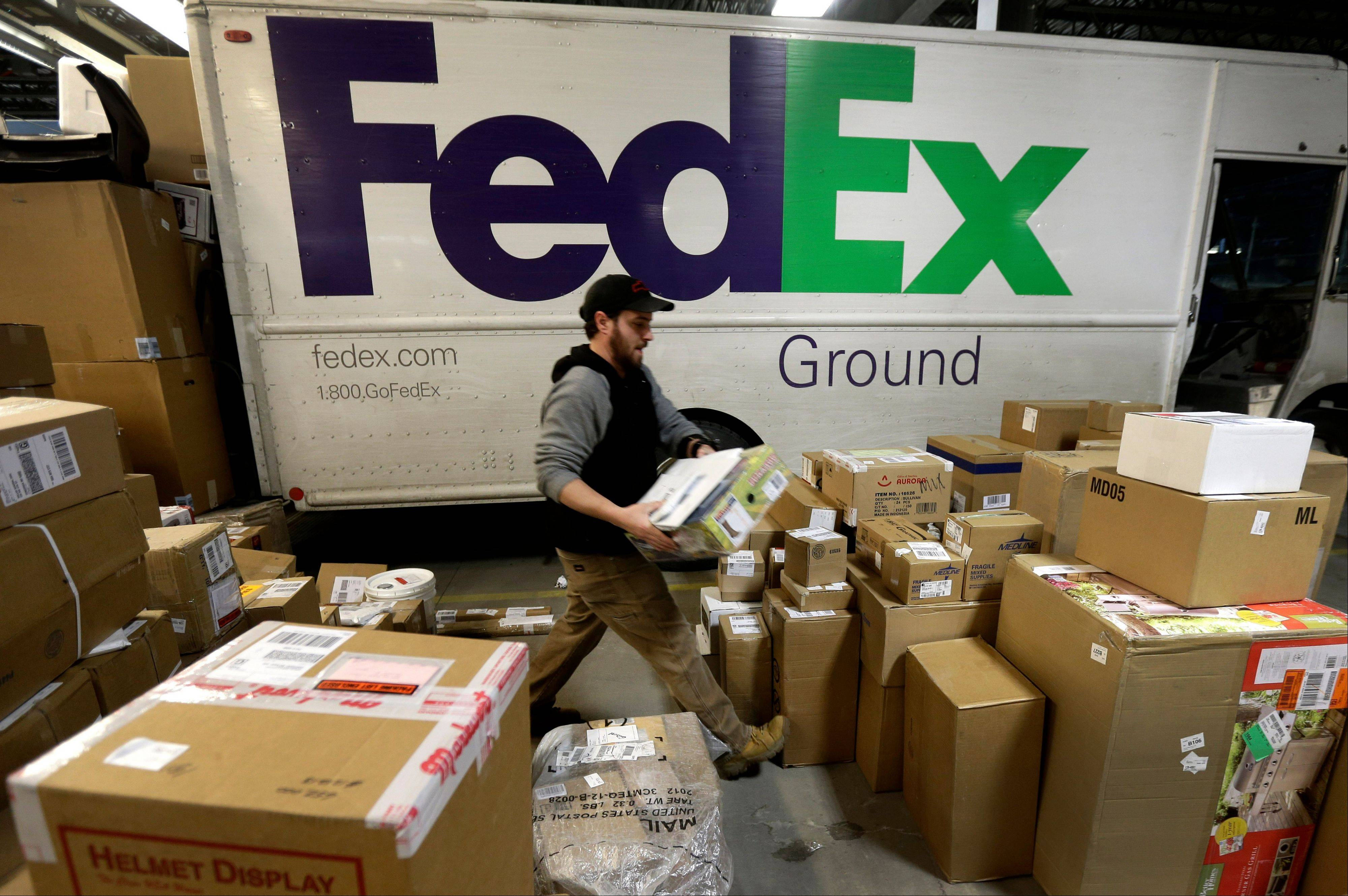 Package handler Chris Addison arranges packages before loading a delivery truck at a FedEx sorting facility in Kansas City, Mo., Dec. 16.
