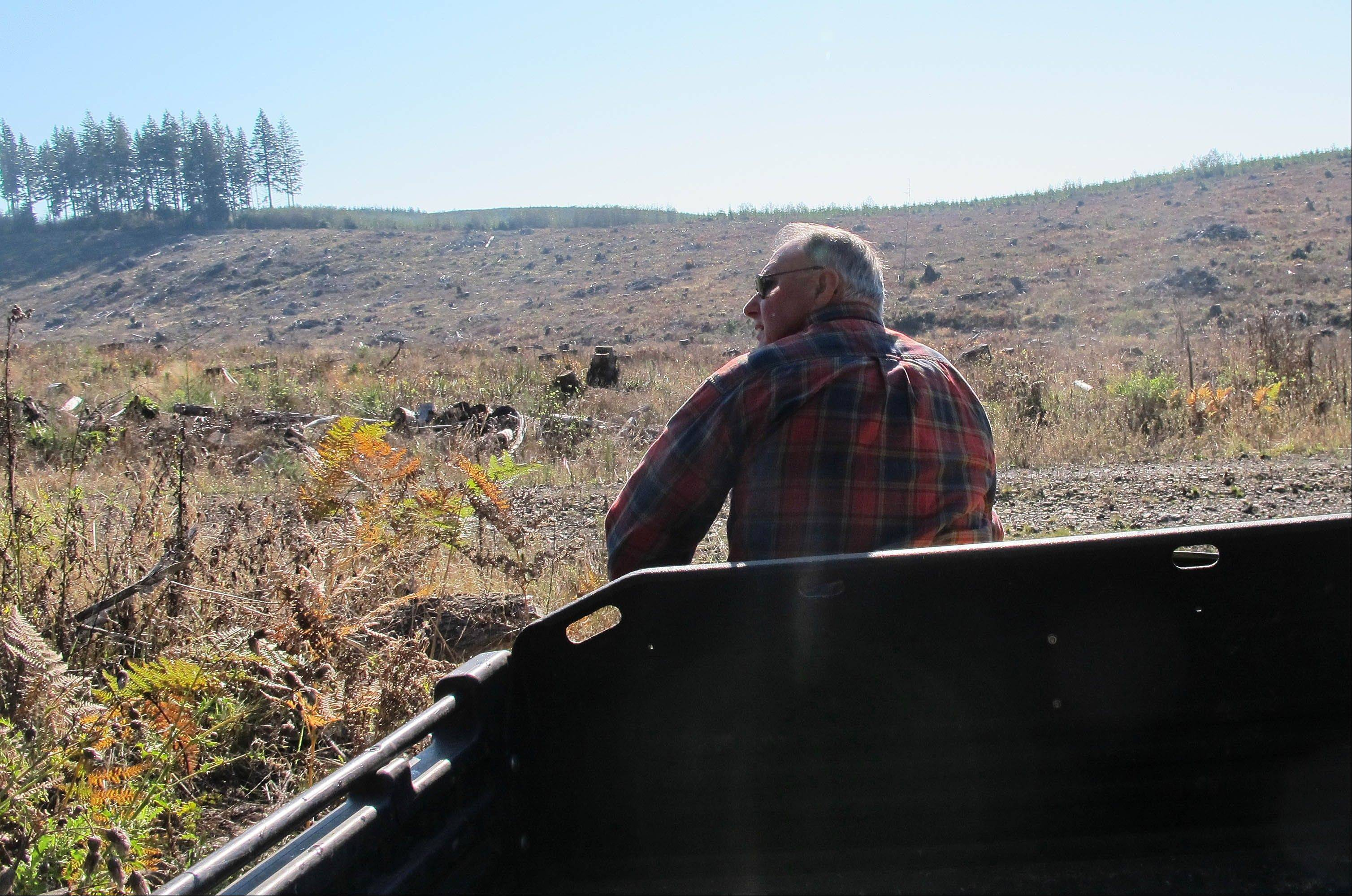 "Paul Nys drives to the edge of his property in Rainier, Ore., where the neighboring property is owned by a timber company. The timber company has completely cleared the hillside of trees, something Nys acknowledges they ""had to do,"" but Nys and a dozen other timber-lot owners are hoping to help cover their medical expenses by selling carbon credits generated by their forest land."