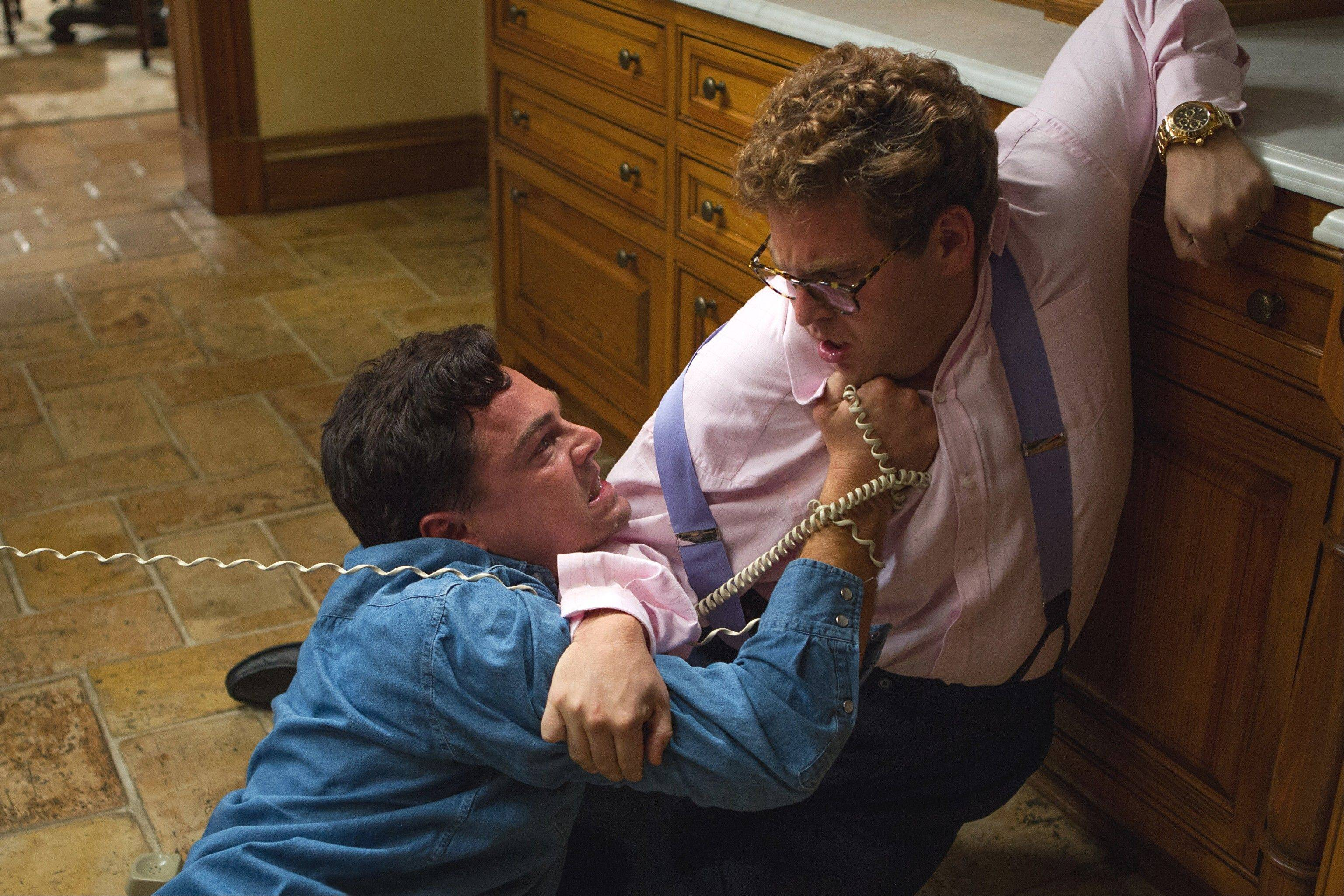 "Jordan Belfort (Leonardo DiCaprio) battles Donnie (Jonah Hill) for the telephone in one of many comic sequences in Martin Scorsese's fact-based movie ""The Wolf of Wall Street."""