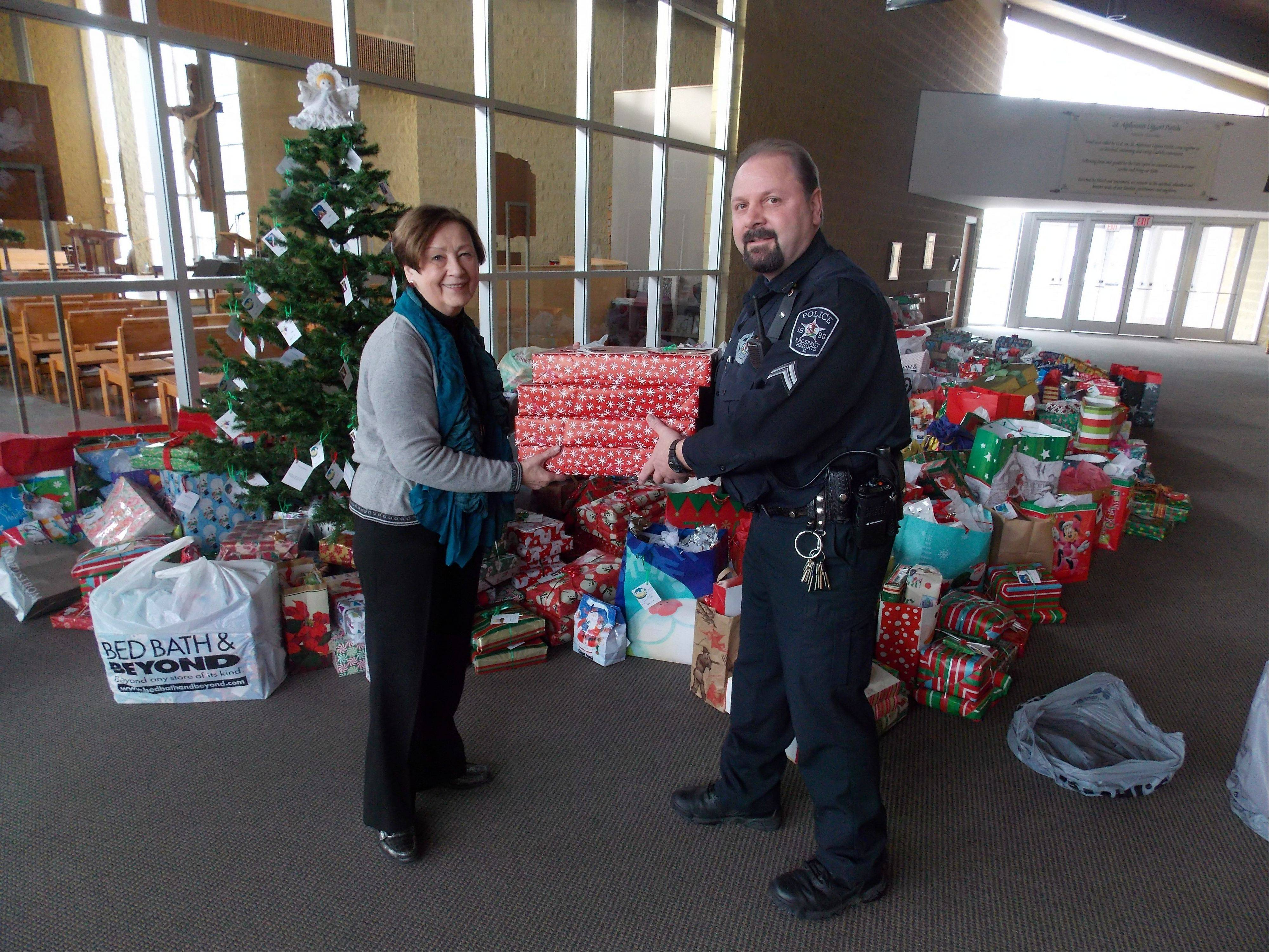 Prospect Heights police Cpl. Scott Minniear and Andrea Ricard of St. Alphonsus Ligouri Parish with gifts donated to the 2013 Giving Tree.