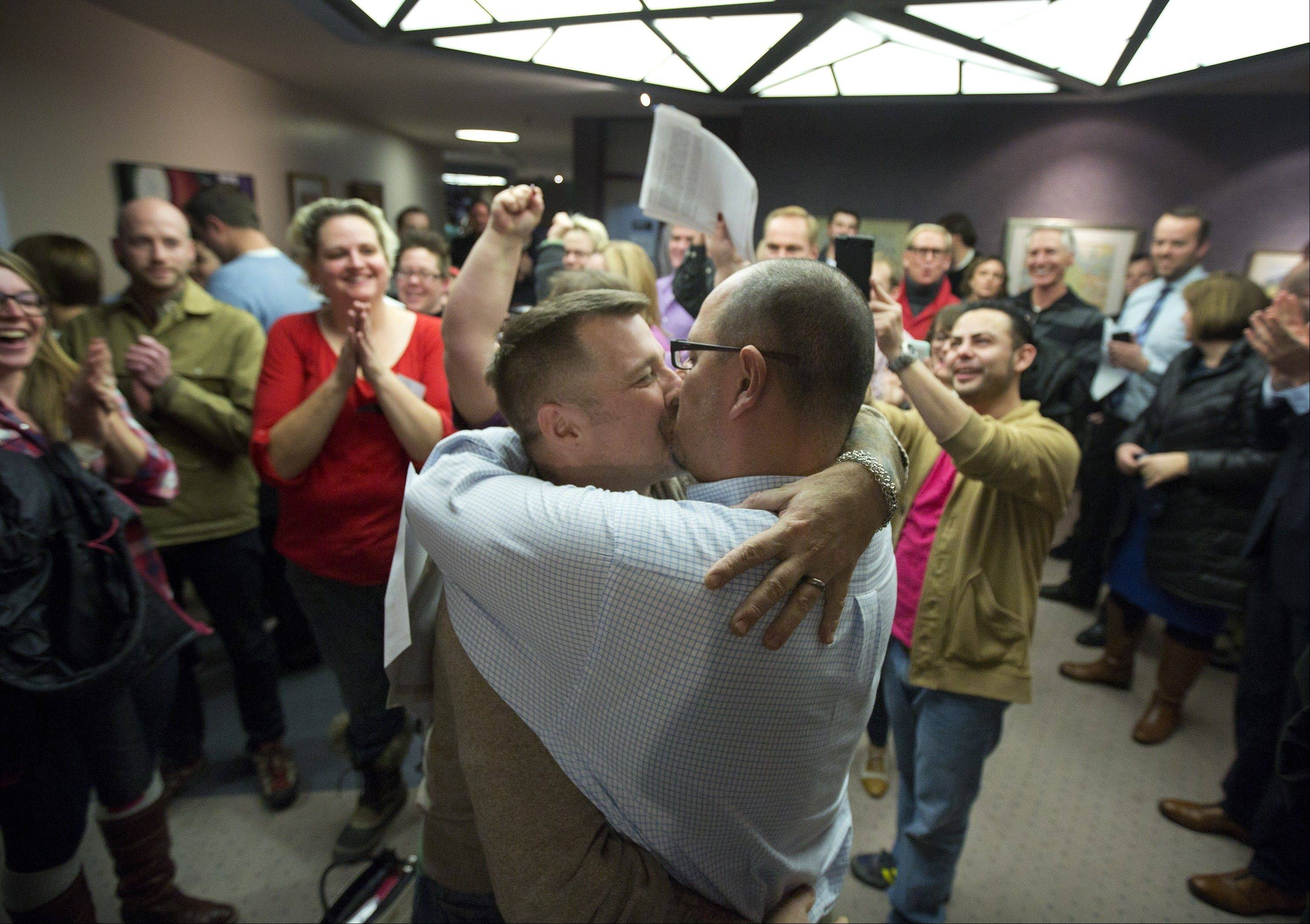 Chris Serrano, left, and Clifton Webb kiss after being married, as people wait in line to get licenses outside of the marriage division of the Salt Lake County Clerk�s Office in Salt Lake City, last Friday.