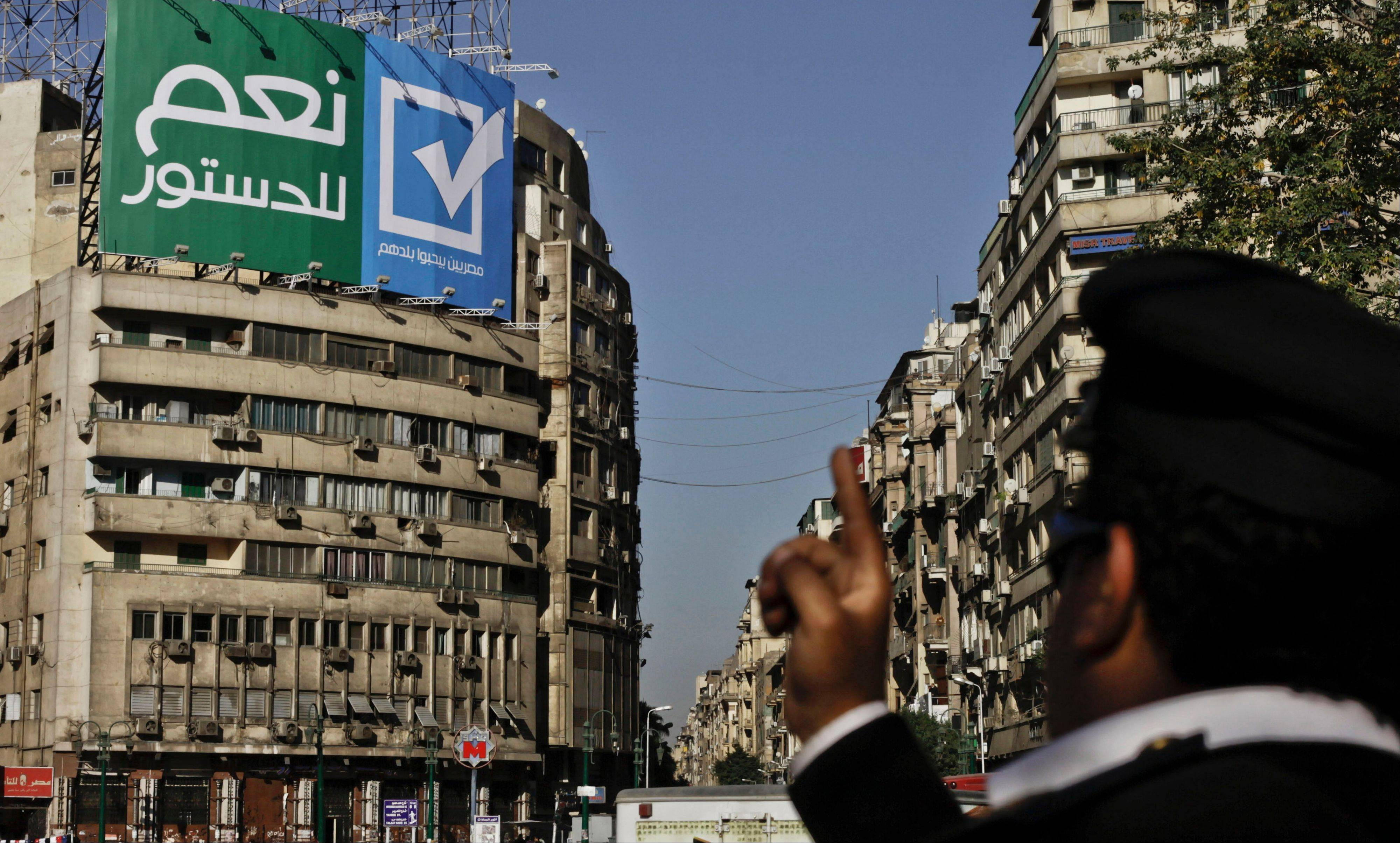 An Egyptian police major general points towards a sign with Arabic that reads, �yes to the constitution, Egyptians love their country,� in Tahrir Square, Cairo, Egypt, Wednesday. The constitutional referendum will be held on Jan. 14 and 15.