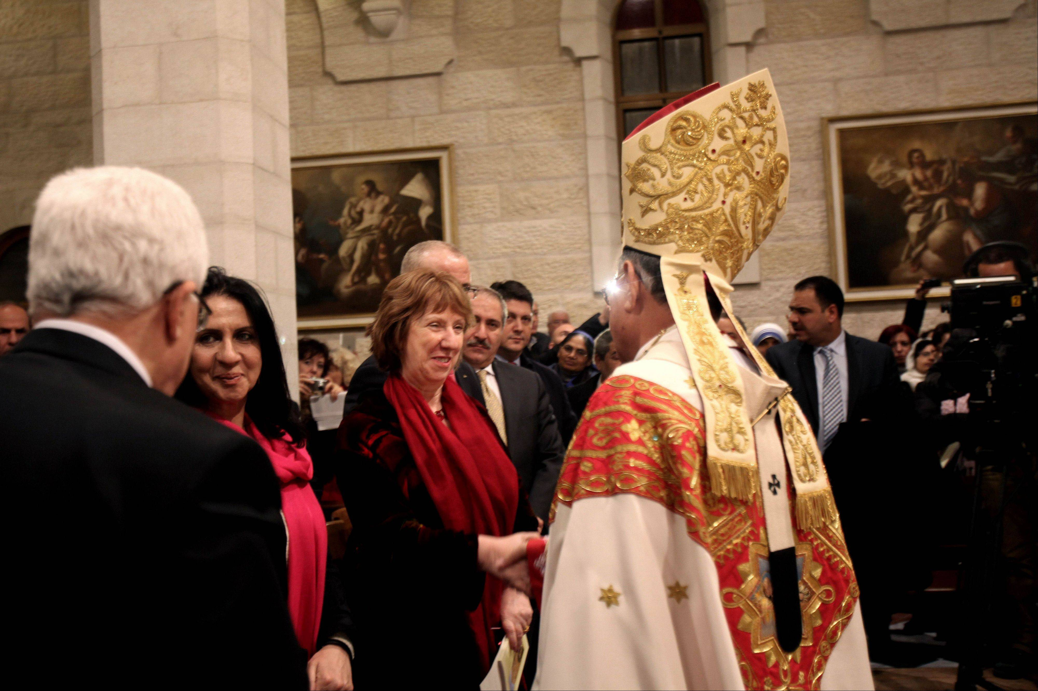 EU foreign policy chief Catherine Ashton, shakes hands with Latin Patriarch of Jerusalem, Fouad Twal, during midnight Christmas mass at the Church of Nativity, traditionally believed by Christians to be the birthplace of Jesus Christ, in the West Bank town of Bethlehem on Christmas Eve, Wednesday, Dec. 25, 2013.