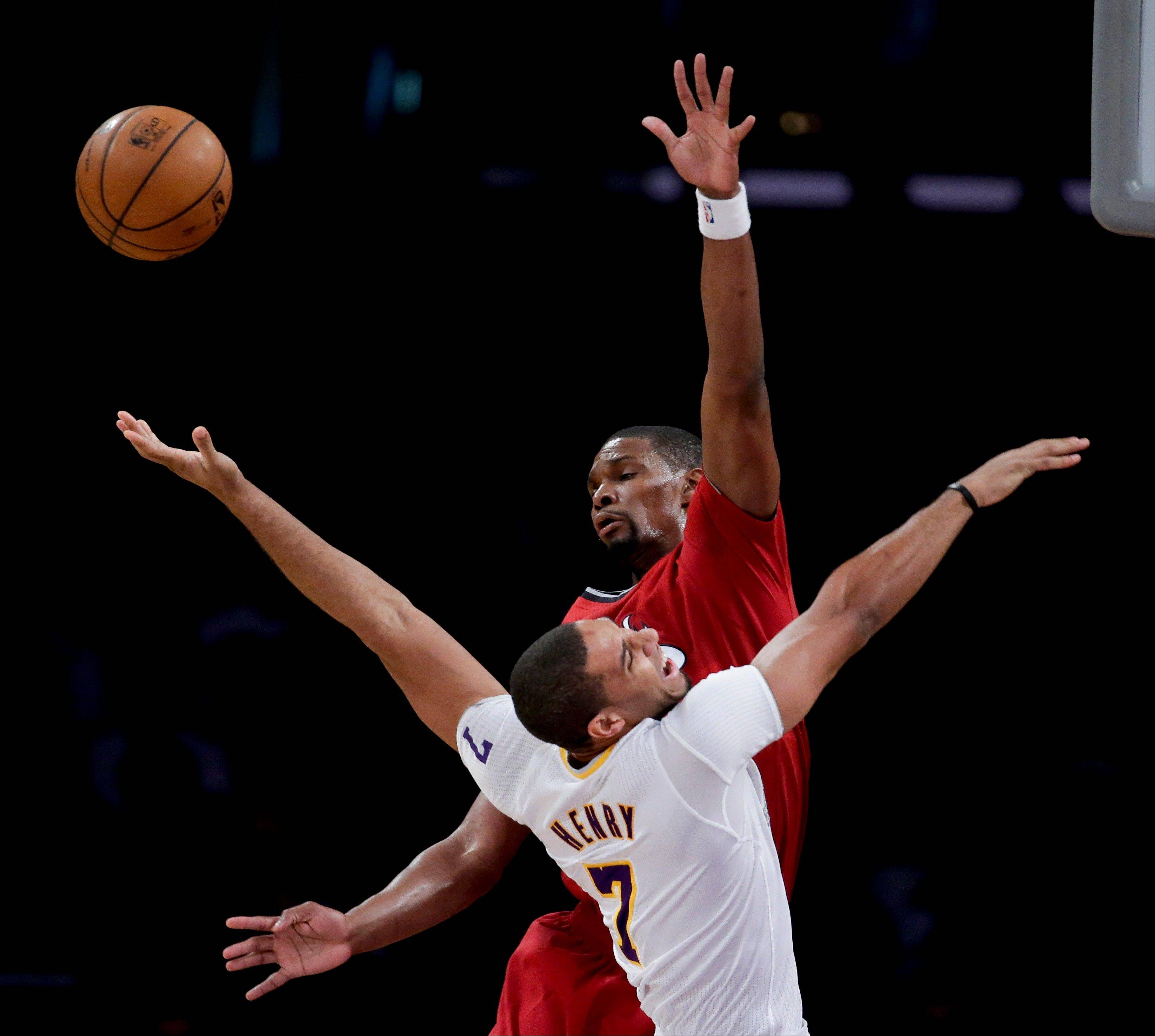 Miami Heat center Chris Bosh, top, blocks a shot by Los Angeles Lakers forward Xavier Henry during the second half of Wednesday�s game in Los Angeles.