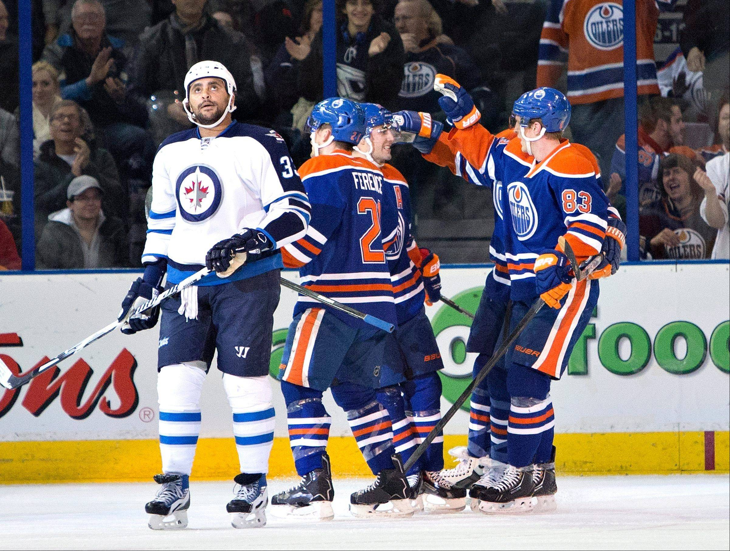 Winnipeg�s Dustin Byfuglien skates away as Edmonton�s Andrew Ference (21), Jordan Eberle (14) and Ales Hemsky (83) celebrate a goal during the first period of Monday�s game in Edmonton, Alberta.