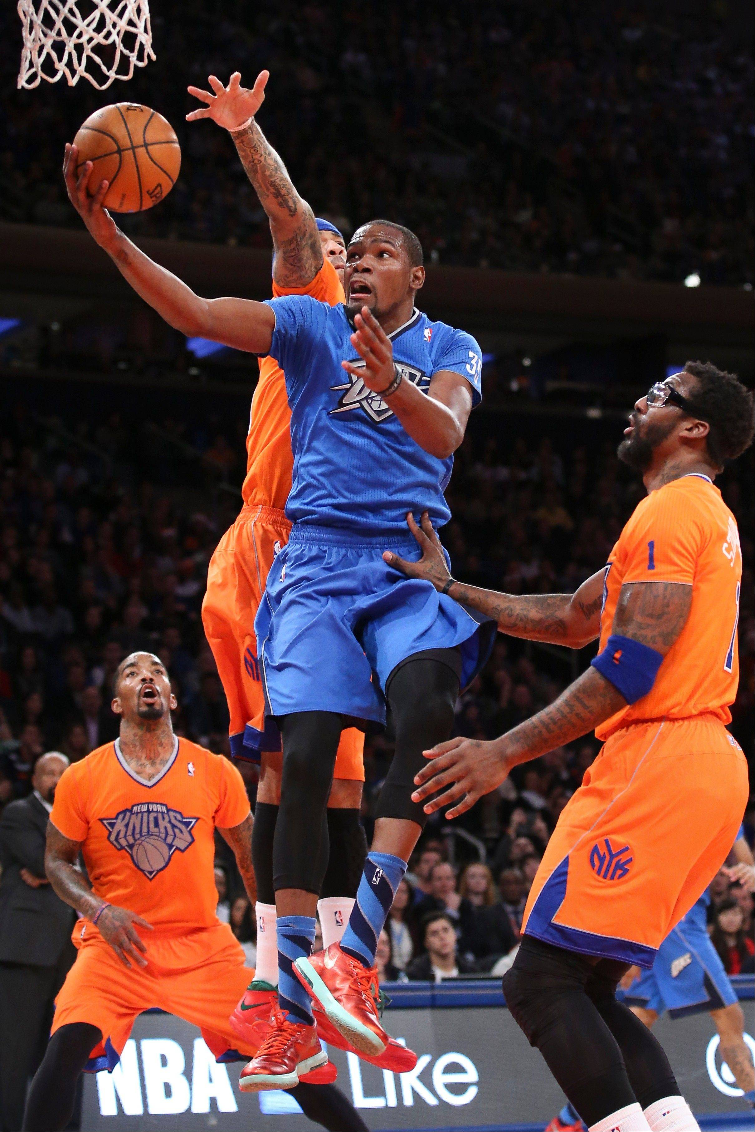Oklahoma City Thunder forward Kevin Durant shoots against New York Knicks forward Kenyon Martin, center, as guard J.R. Smith, left, and forward Amare Stoudemire watch during the second half of Wednesday�s game at Madison Square Garden.