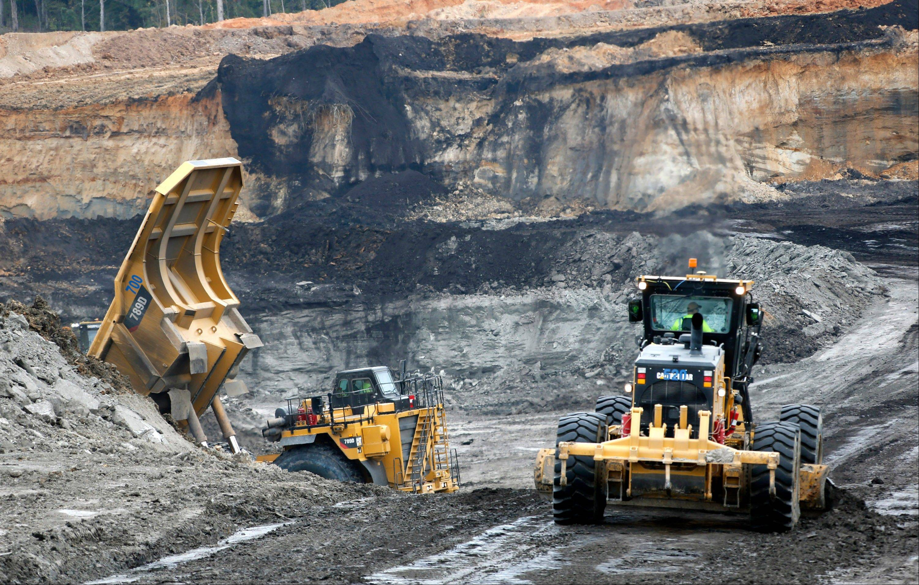 An earth mover, and a dump truck move through the open lignite pit at Liberty Mine adjacent to the Mississippi Power's Kemper County energy facility in central Mississippi near DeKalb. The plant, America's newest, most expensive coal-fired power plant is hailed as one of the cleanest on the planet, thanks to government-backed technology that removes carbon dioxide and keeps it out of the atmosphere. Once the carbon is stripped away, it will be used to do something that is not so green at all -- extract oil. Power companies sell the carbon dioxide to oil companies, which pump it into old oil fields to force more crude to the surface.