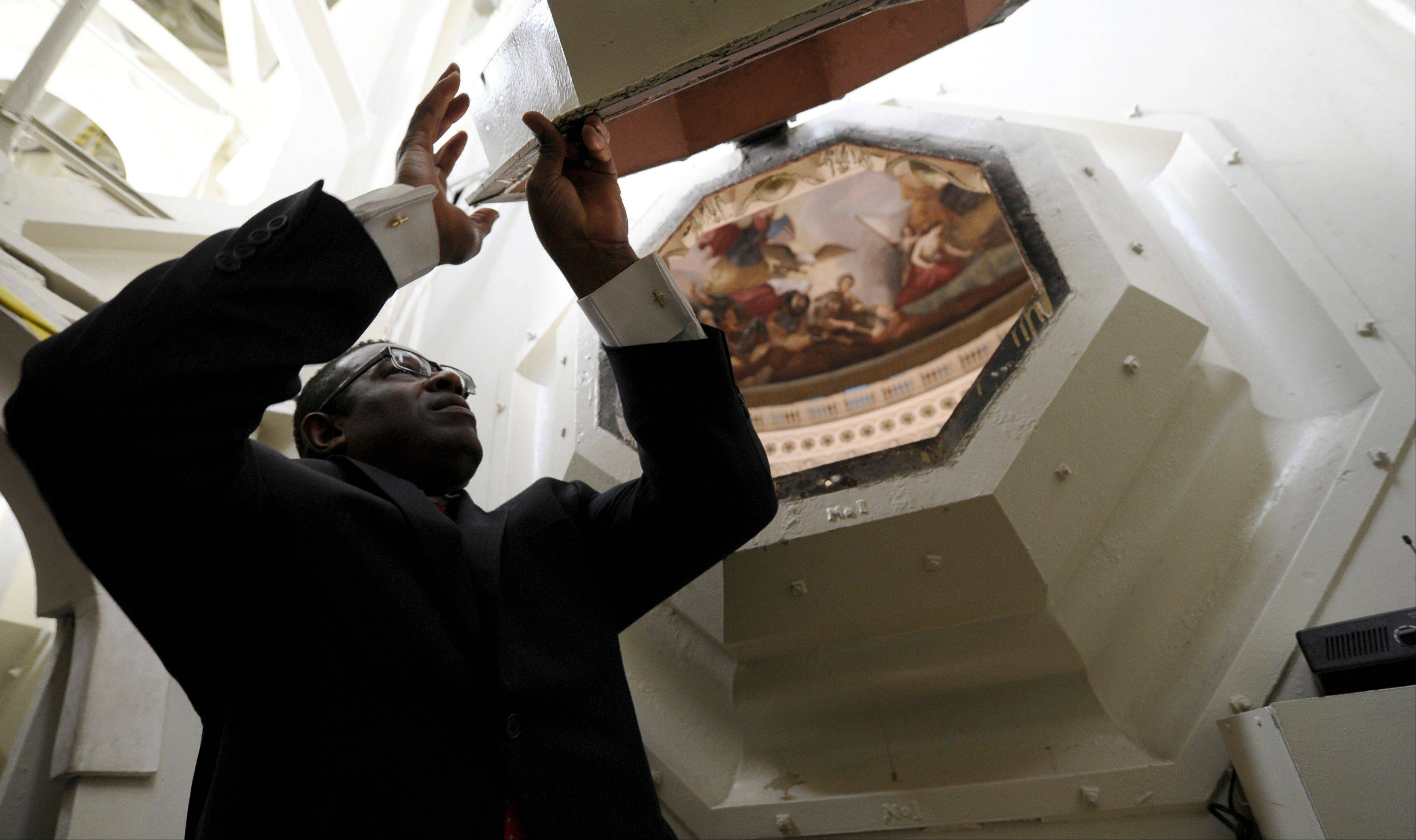 Eugene Poole Jr., a project manager for the Capitol dome restoration project, lifts one of the coffer windows in the ceiling of the Capitol dome during a media tour on Capitol Hill in Washington. A world-famous symbol of democracy is going under cover, as workers start a two-year, $60 million renovation of the U.S. Capitol dome.