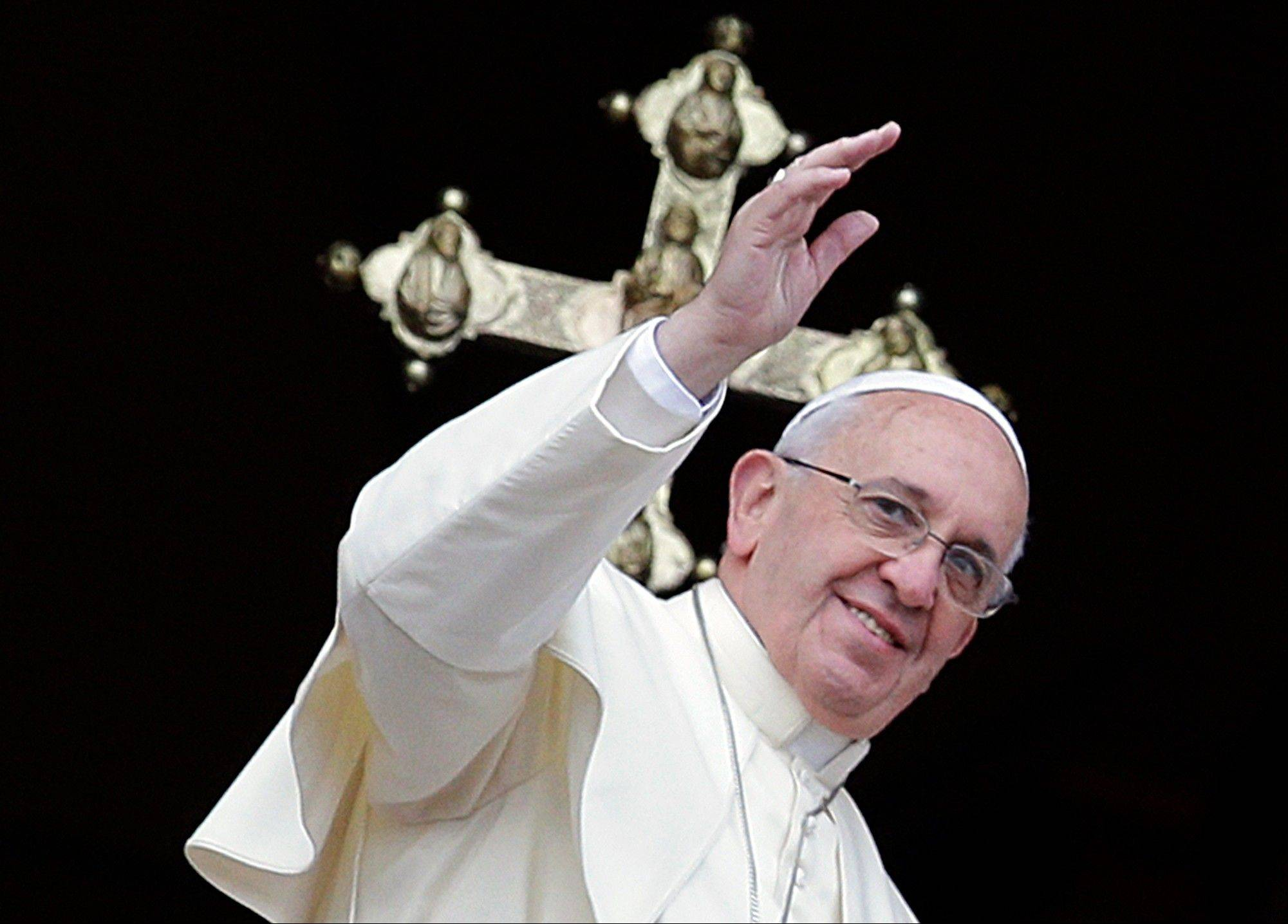 "Pope Francis delivers his ""Urbi et Orbi"" (to the City and to the World) message from the central balcony of St. Peter's Basilica at the Vatican, Wednesday. Francis wished for a better world, with peace for the land of Jesus' birth, for Syria and Africa, as well as for the dignity of migrants and refugees fleeing misery and conflict."