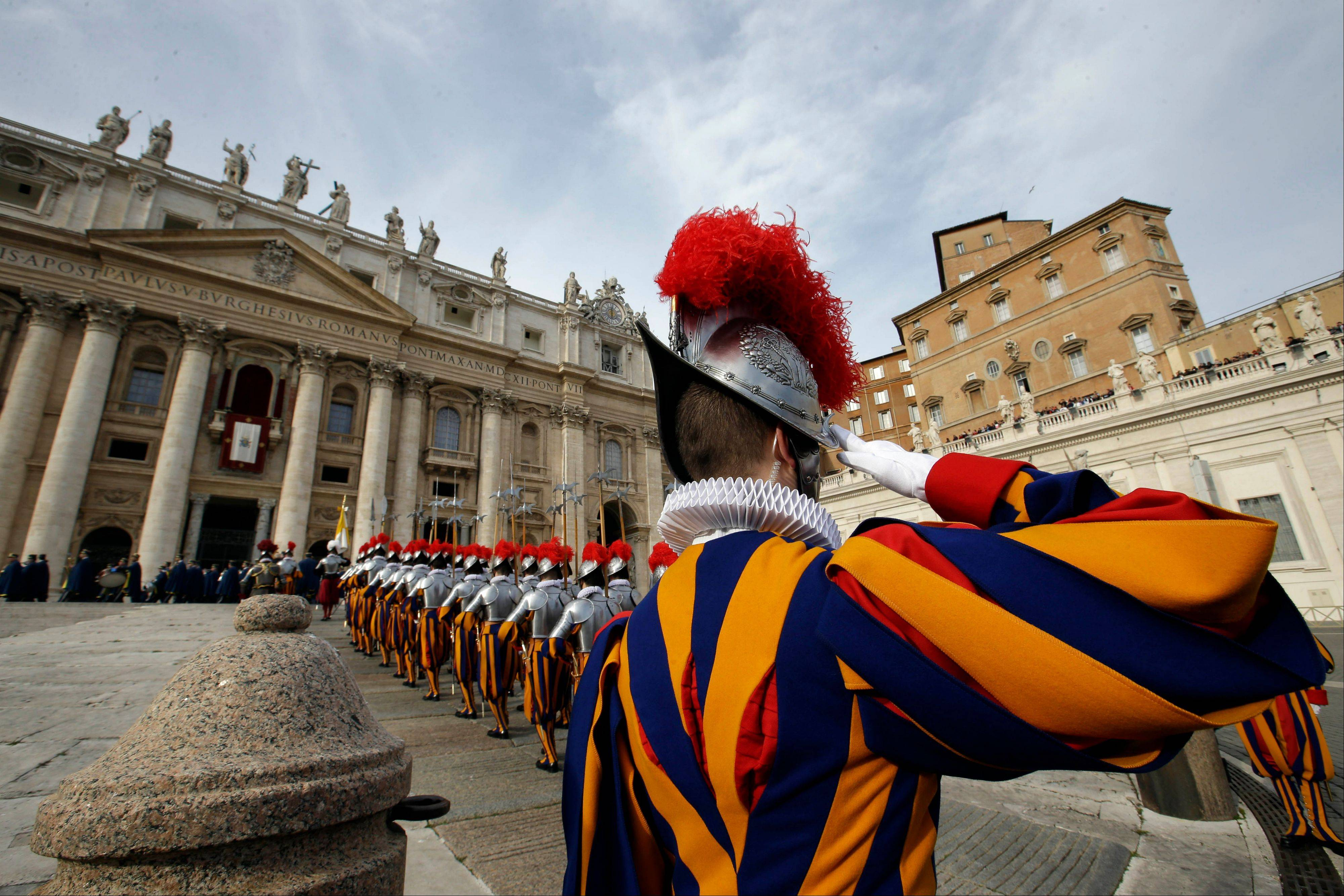 "Swiss guards march prior to the start of Pope Francis ""Urbi et Orbi"" (to the City and to the World) message he delivered from the central balcony of St. Peter's Basilica at the Vatican, Wednesday. Francis wished for a better world, with peace for the land of Jesus' birth, for Syria and Africa, as well as for the dignity of migrants and refugees fleeing misery and conflict."