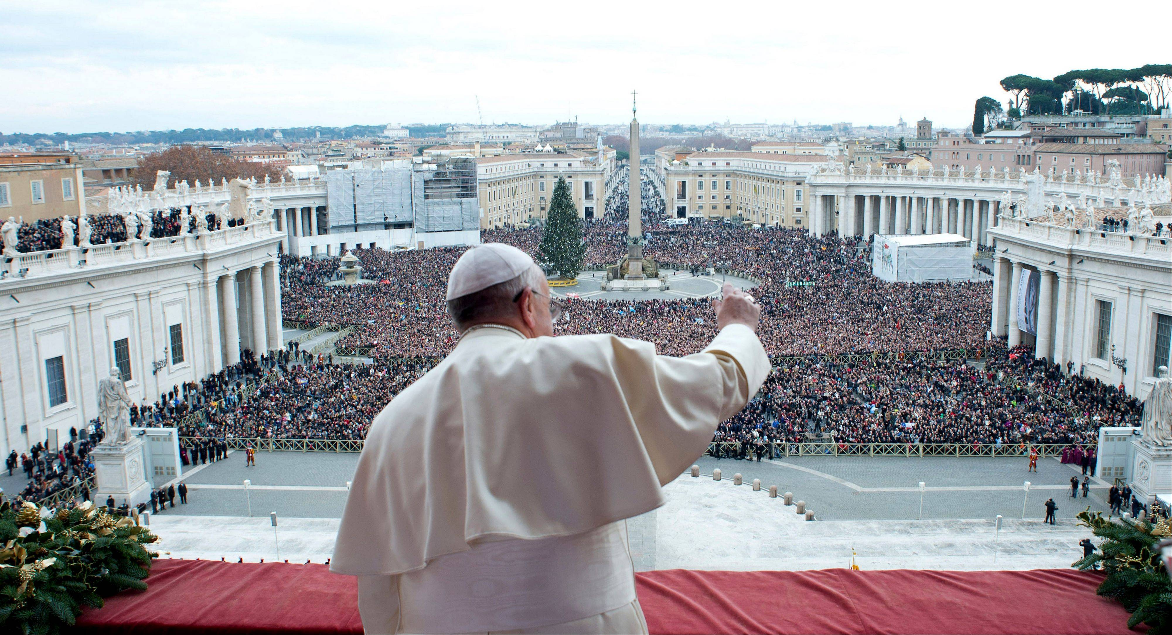 "In this picture provided by the Vatican newspaper L'Osservatore Romano, Pope Francis delivers his ""Urbi et Orbi"" (to the City and to the World) message from the central balcony of St. Peter's Basilica at the Vatican, Wednesday, Dec. 25, 2013."