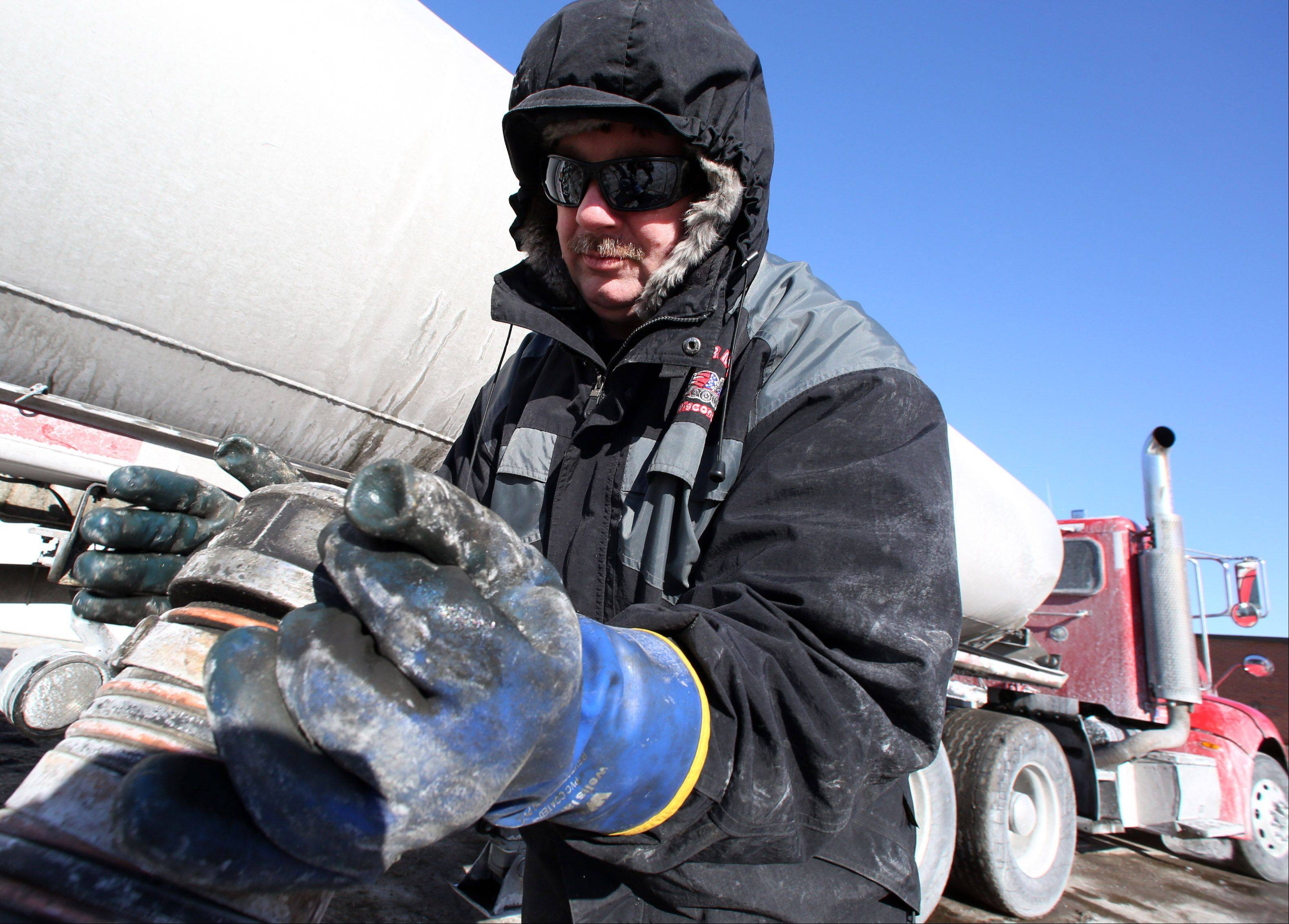 Rob Szymkowski, with Burke Transport Service in Libertyville, places a gas line hose back on to his truck after delivering diesel fuel to IDOT in Arlington Heights.