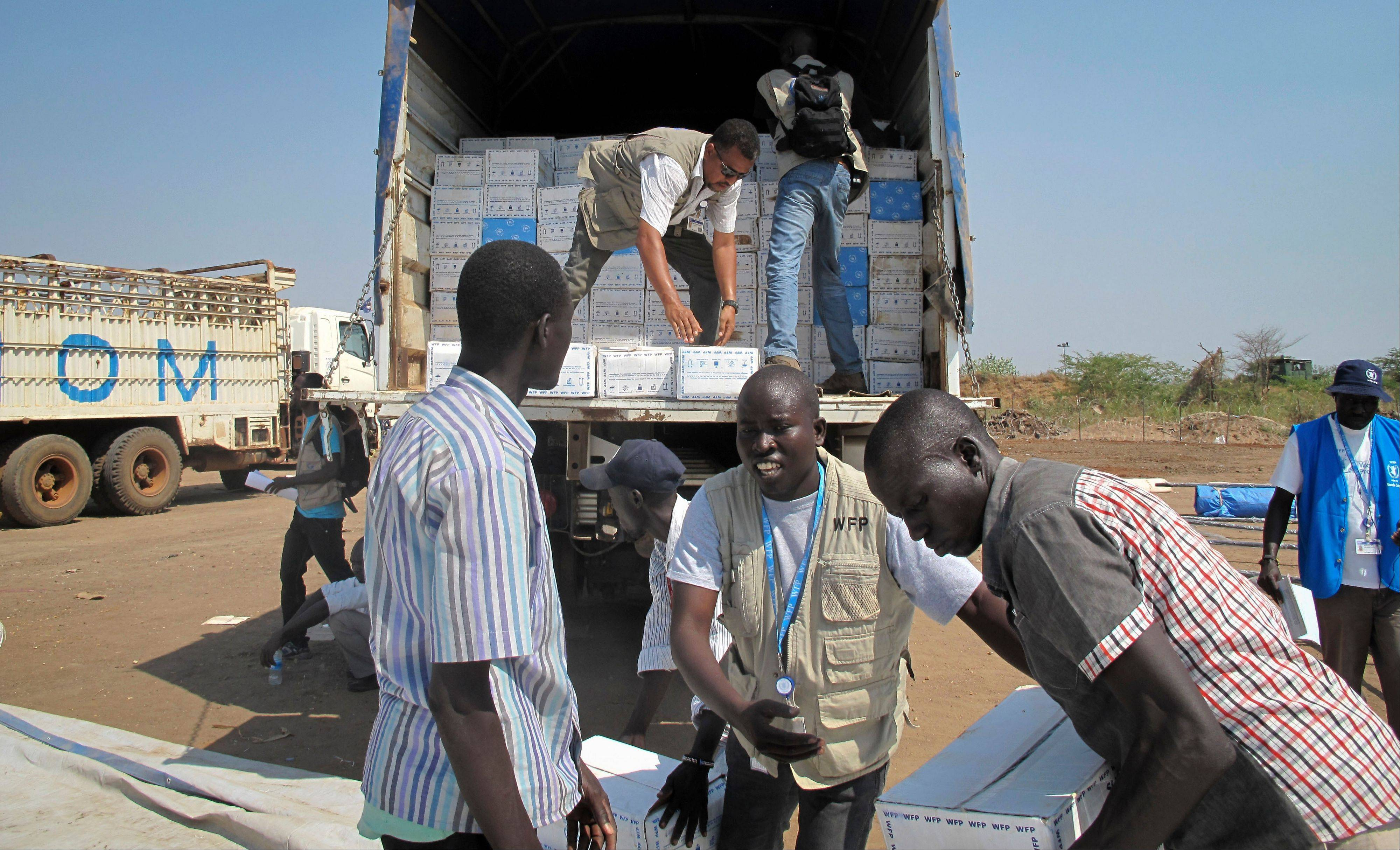 World Food Programmestaff and helpers unload a truck of cereal food assistance at a U.N. compound Tuesday where many displaced have taken shelter in Juba, South Sudan.