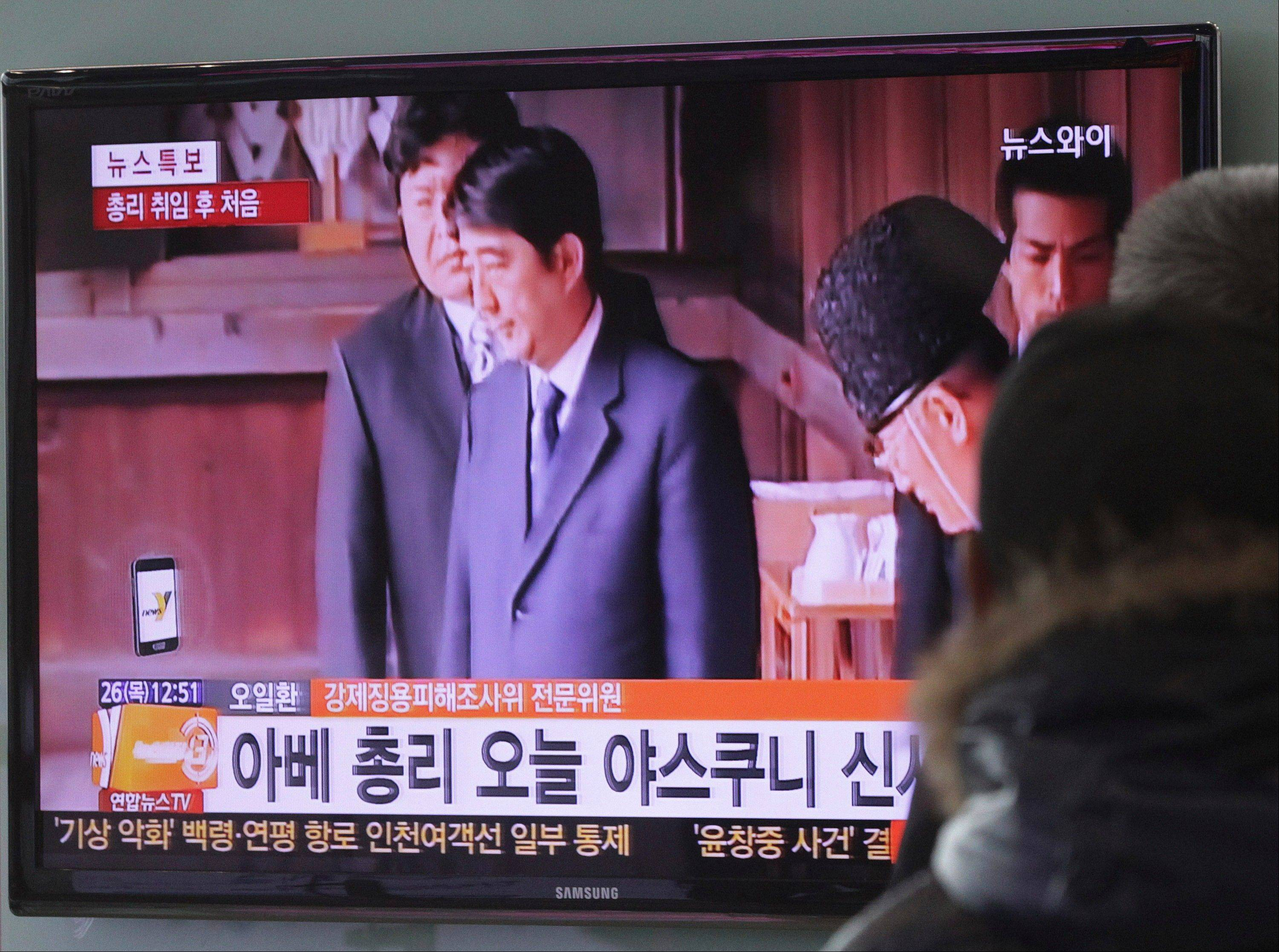 People watch a TV news program on Japanese Prime Minister Shinzo Abe�s war shrine visit, at the Seoul Railway Station in Seoul, South Korea, Thursday. Abe paid his respects Thursday at a shrine honoring Japan�s war dead in a move that drew sharp rebukes from both China and South Korea who warned that the visit celebrates his country�s militaristic past and heightens concerns that Japan may veer back in that direction.