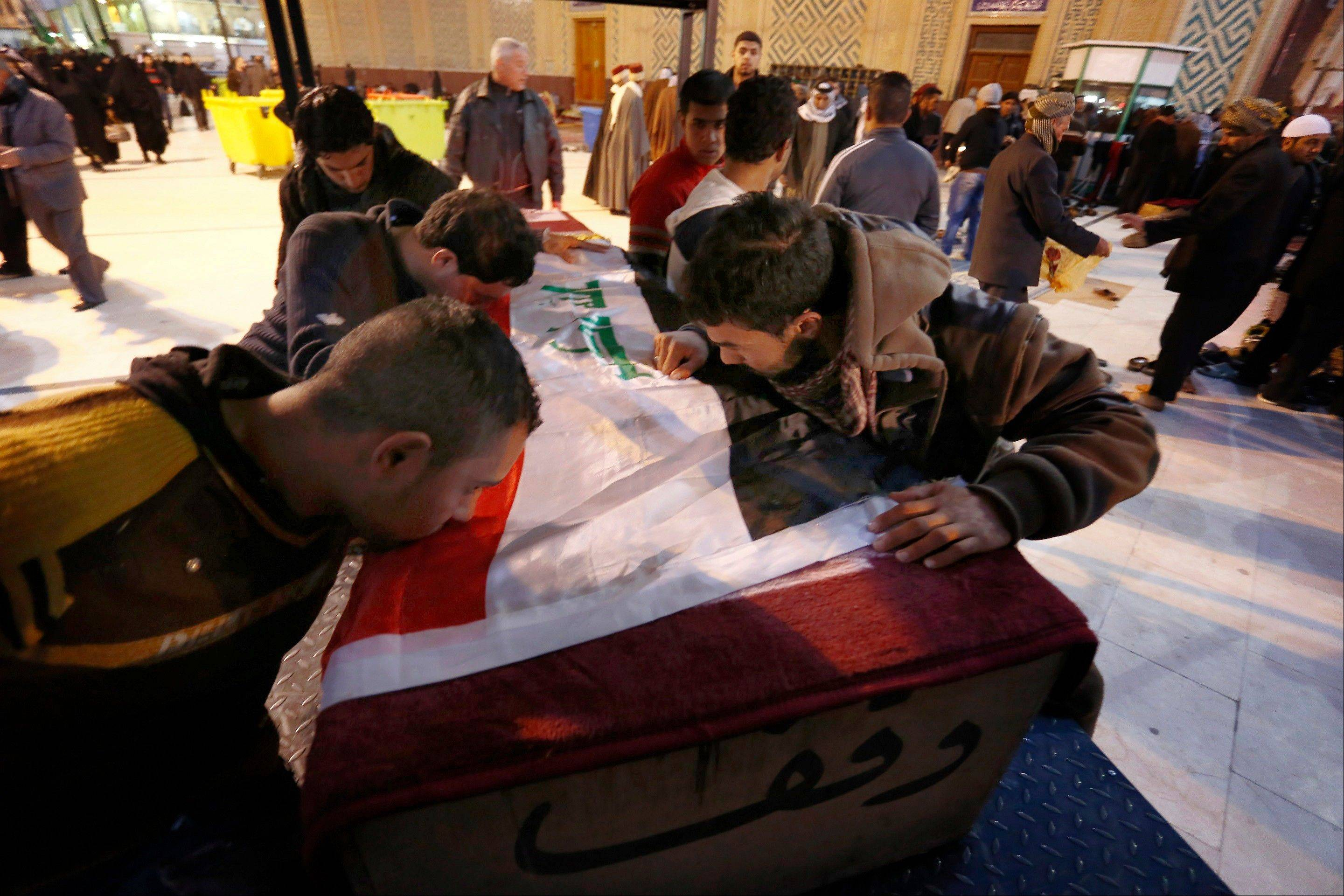 Sons of an Iraqi killed man, Karim Nasim, react during his funeral in the Shiite holy city of Najaf, 100 miles south of Baghdad, Iraq, Thursday. Nasim was killed in a bombing at a vegetable market in Baghdad on Wednesday. According to U.N. estimates, more than 8,000 people have been killed since the start of the year.