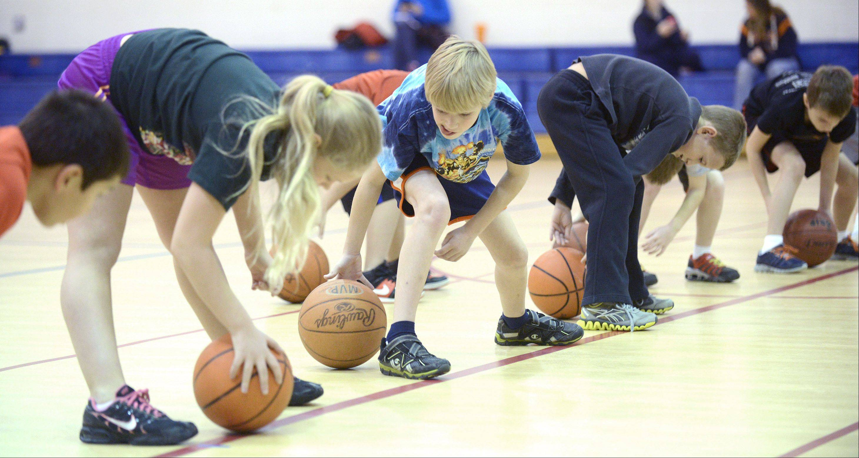 Madison Kozlowski, 10, of Aurora and Logan Hubble, 8, of Sugar Grove practice dribbling through and around their legs during the start of a three-day basketball camp in Sugar Grove on Thursday, December 26. The park district camp, run by All Stars Sports Instruction, included basic mechanics with concentrations on shooting, ball handling and passing.