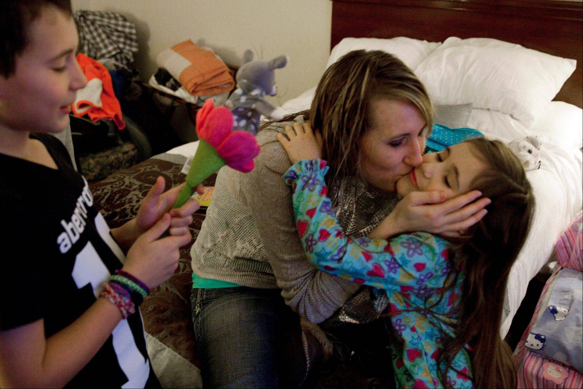 Jill Ghantous kisses her daughter, Briana Ghantous, 6, at the Wingate Hotel in Grand Blanc Township, Mich. The Ghantous family lost power on Sunday at their home in Swartz Creek due to ice storms that have left about 40,000 people in Genesee County without power.