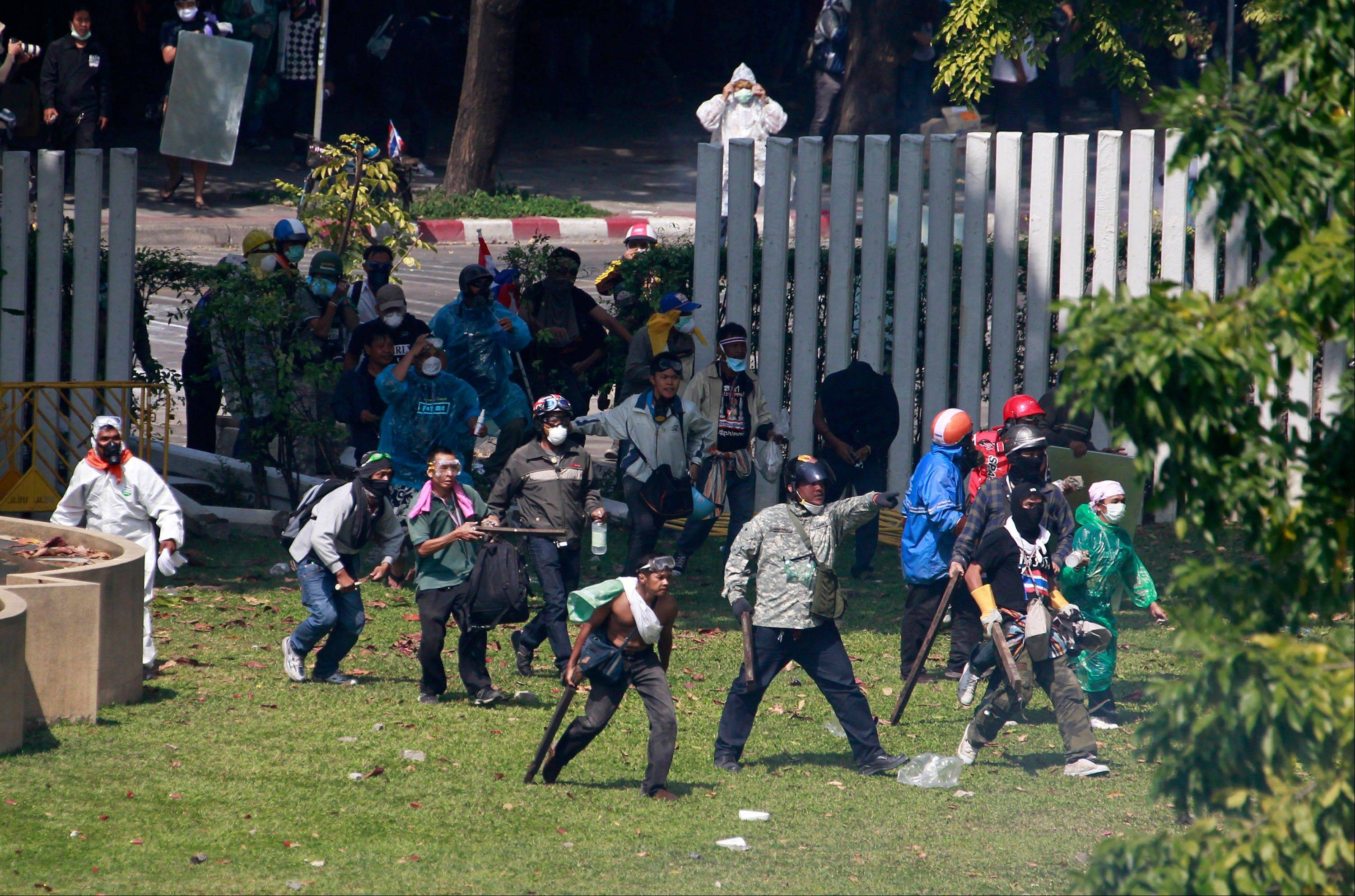 Thai anti-government protesters enter a sport stadium during a clash with riot policemen in Bangkok, Thailand, Thursday.